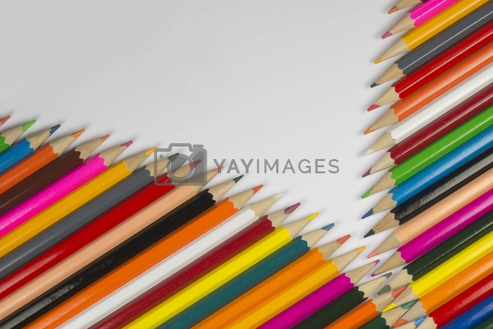 Abstract composition of a set cedar wooden colour pencils against a white background in zipper style
