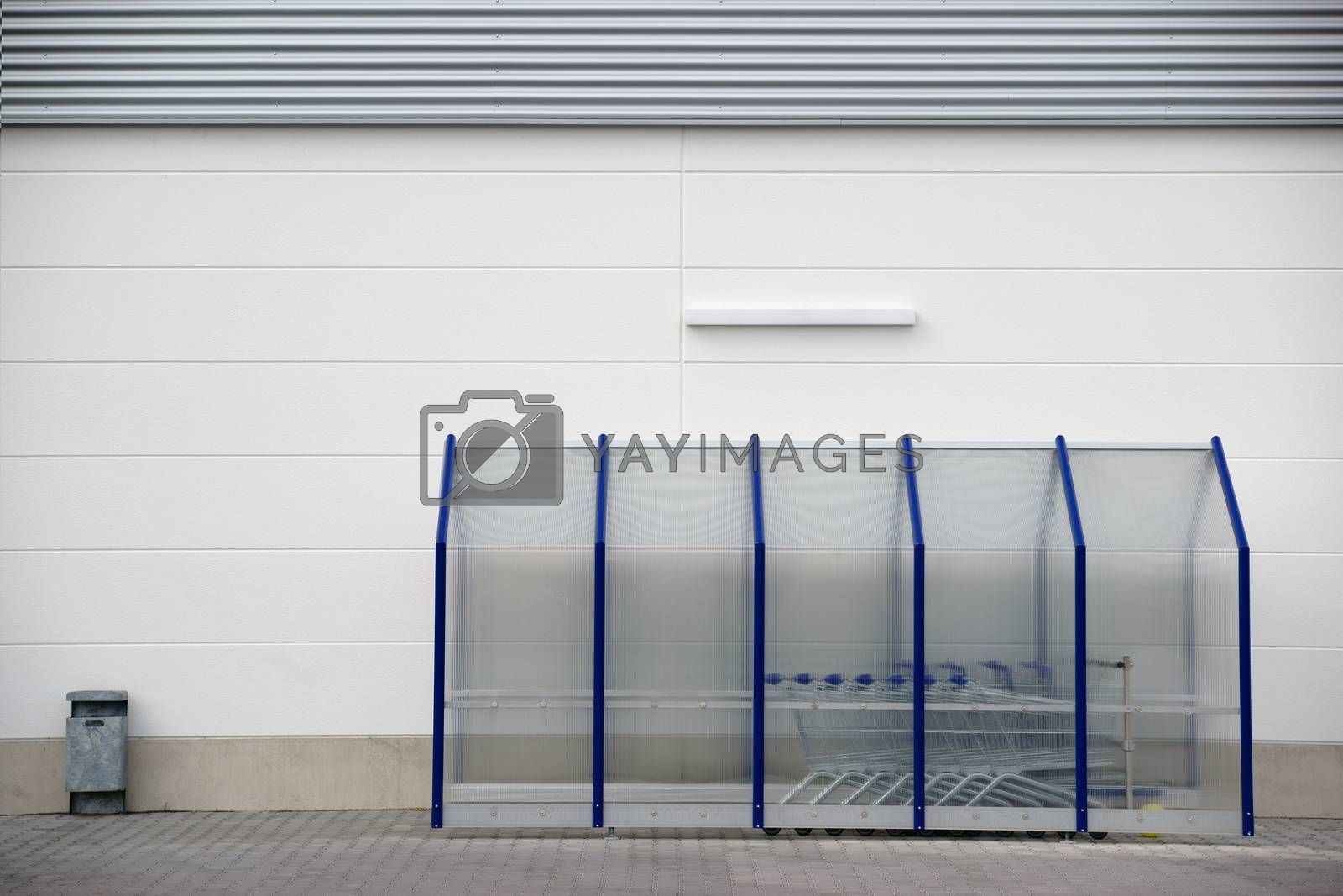 A plastic shelter with shopping baskets and a garbage container on the wall of a shopping mall.