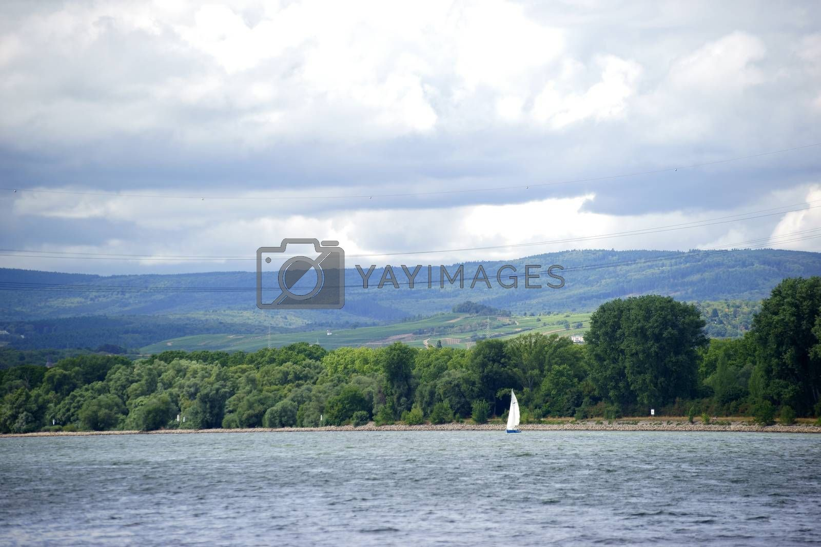 A sailboat sailing on the river Rhine in front of of the Taunus mountain range during a weather change.