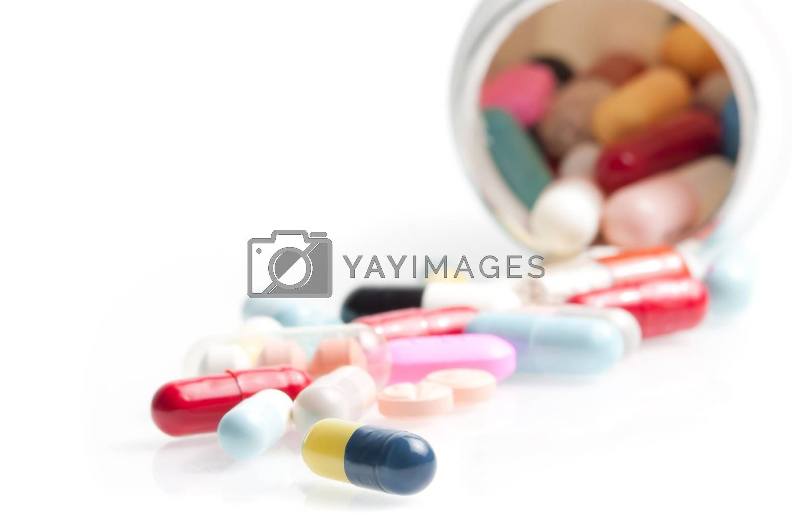 colored pills in laboratory near white container on white table with space for text