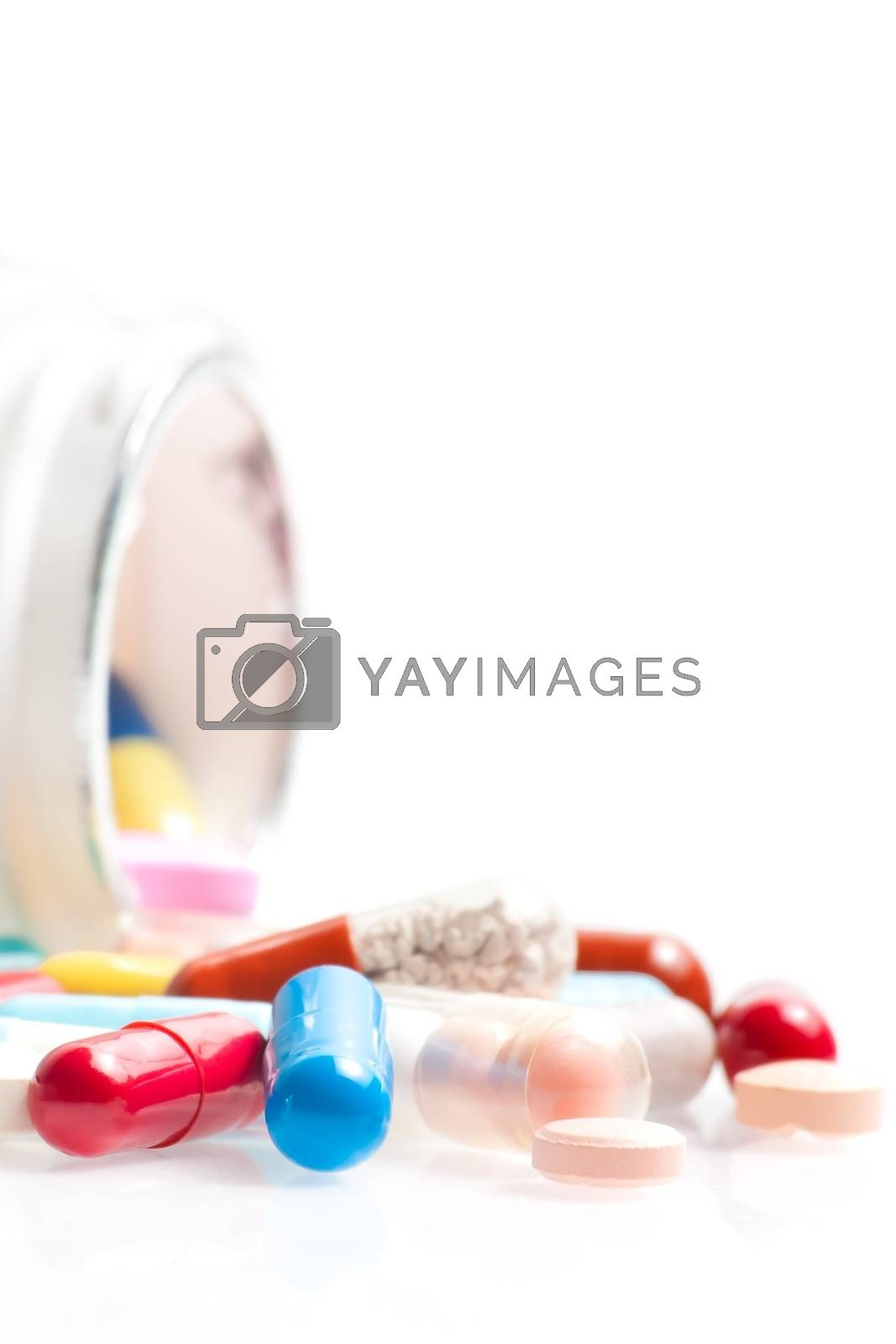 colored pills in laboratory in front of a white container on white table