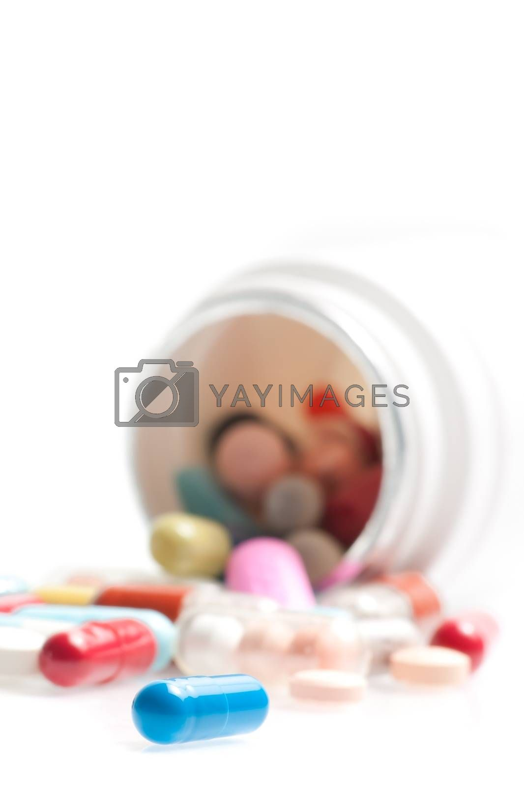 blue pill in laboratory in front of a colored pills on white table