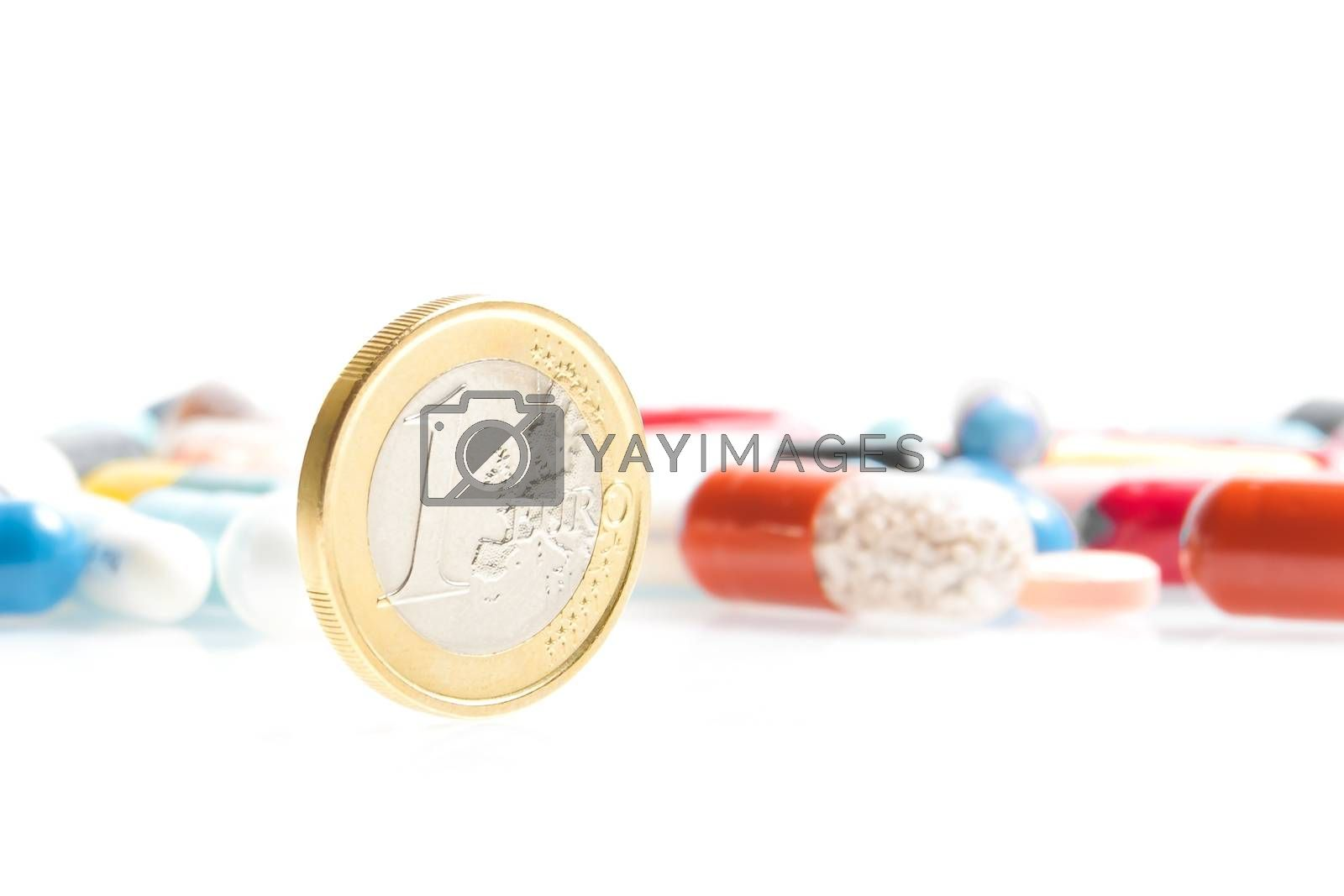 euro coin in front of medical pills on white background