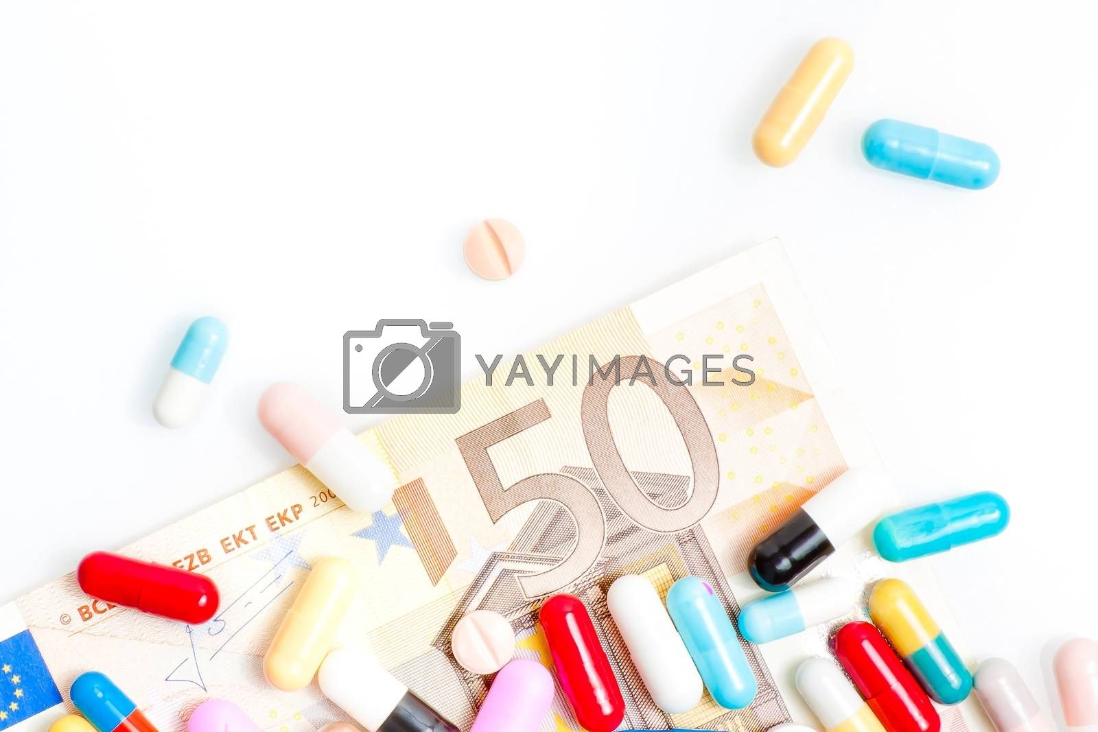 medical pills over fifty euro banknote on white background