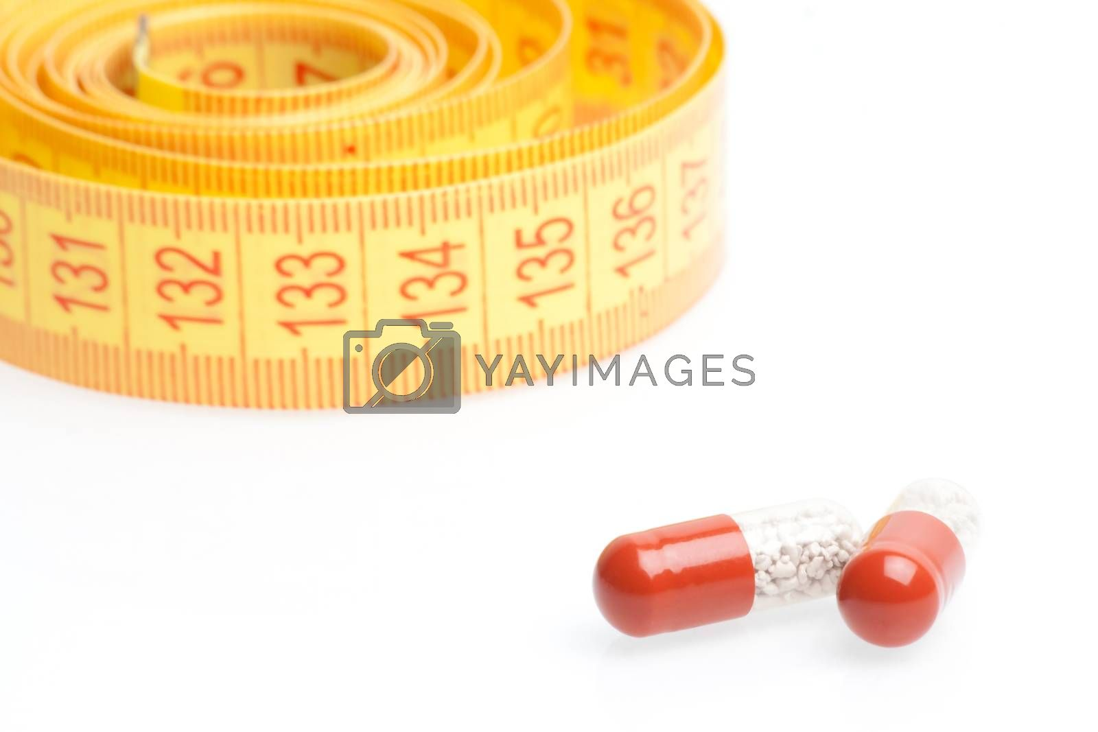 medical pills for dieting in front of measuring tape on a white background