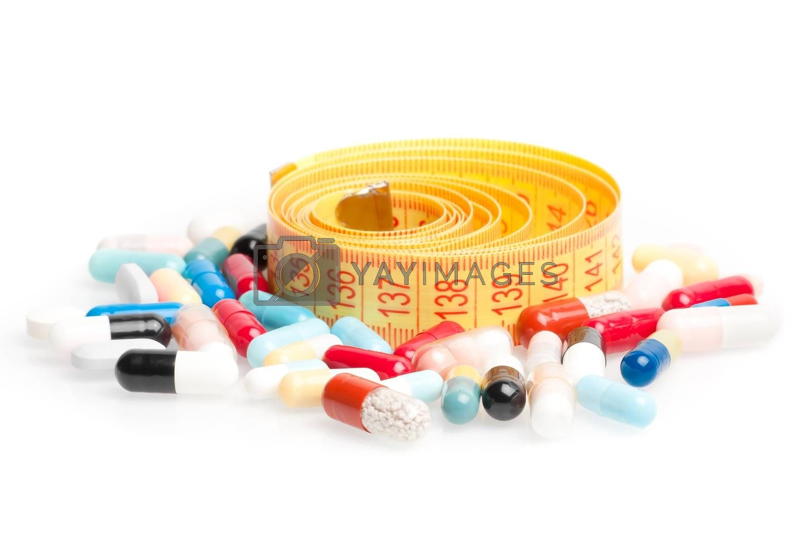 measuring tape with pills for dieting around on a white background