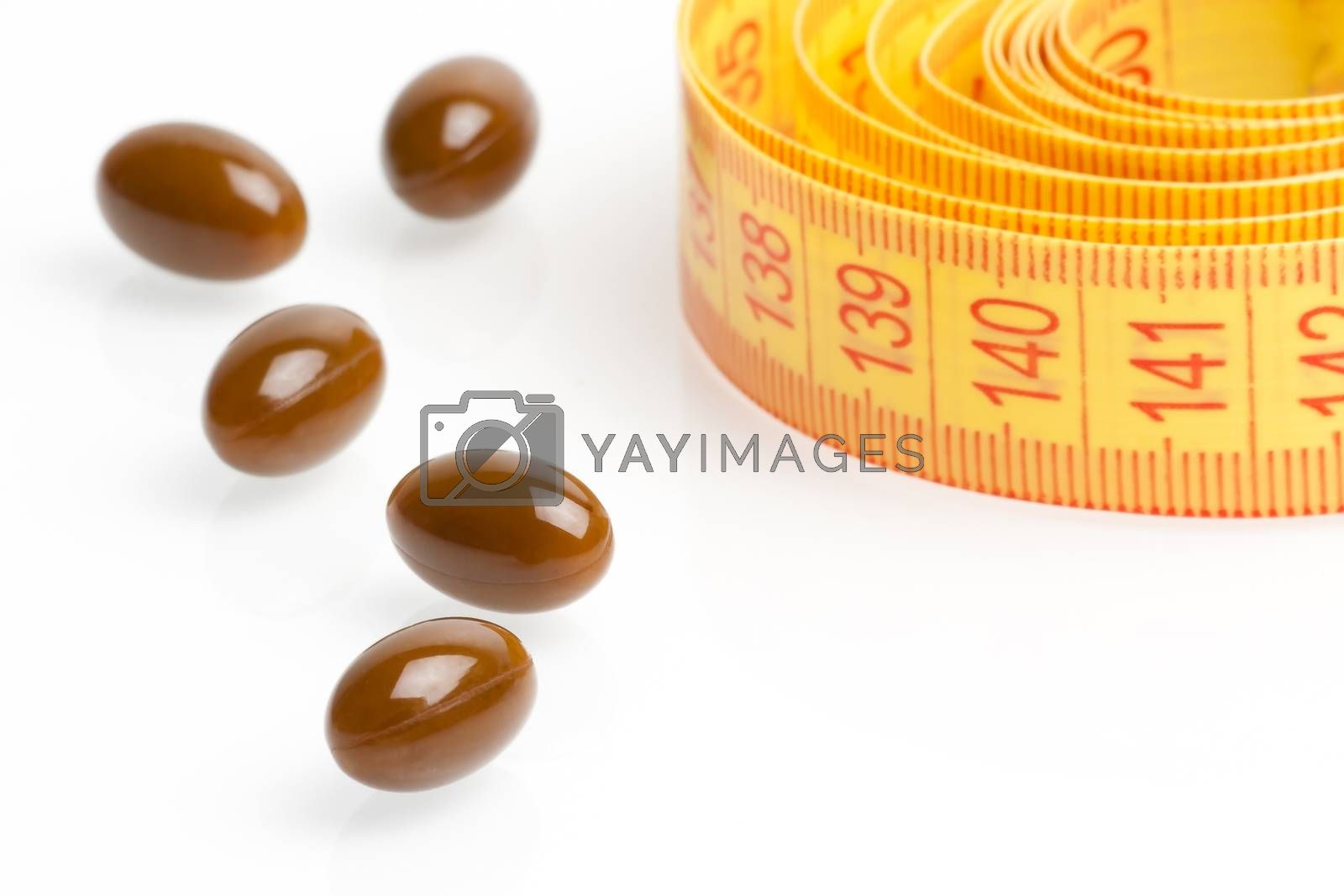 brown medical pills for dieting in front of measuring tape on a white background