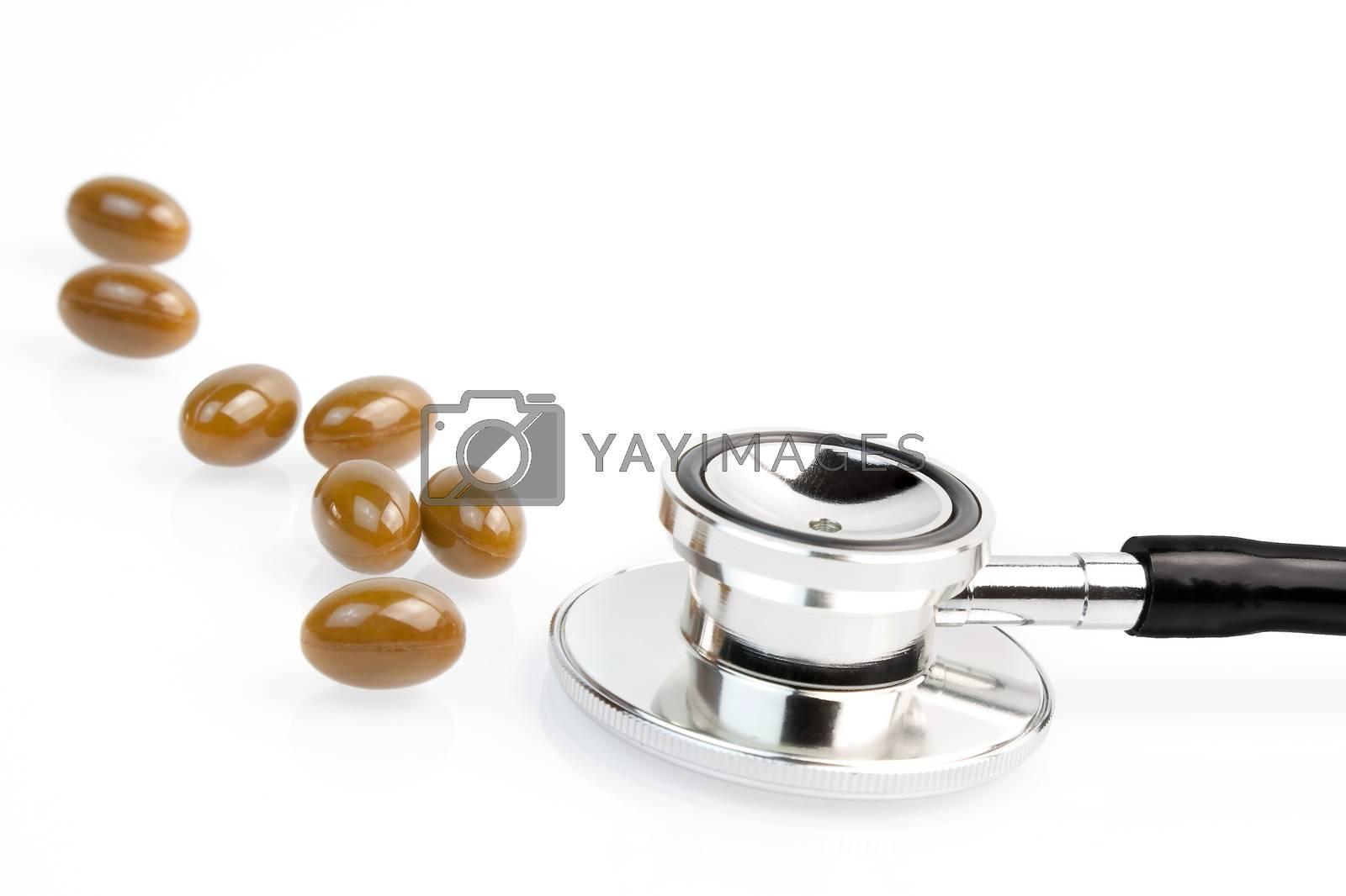 medical pills near stethoscope on white background