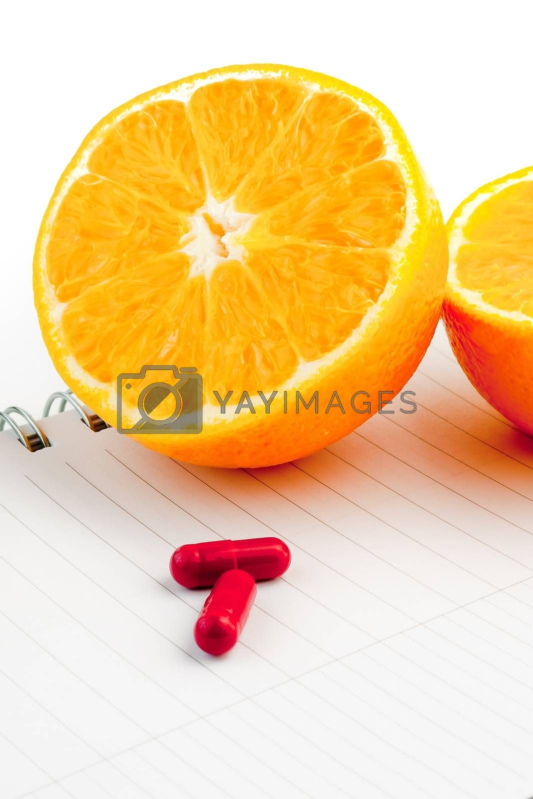 detail an orange and capsule on notepad