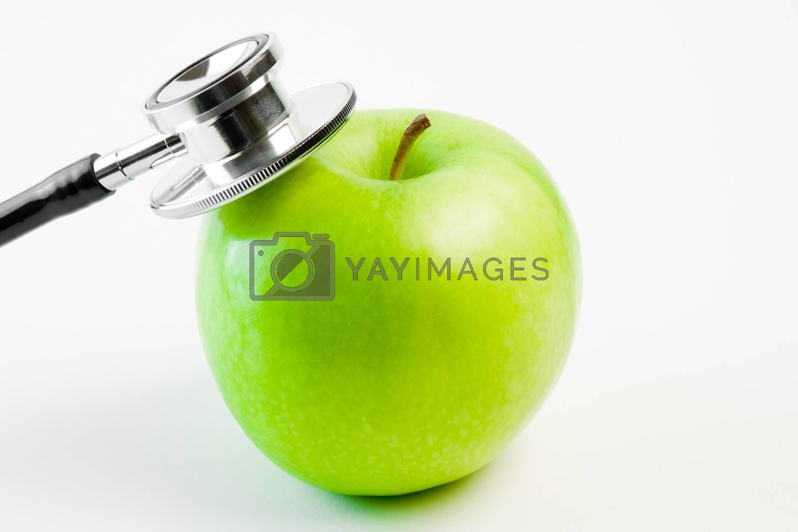 detail of medical stethoscope and apple on a white background
