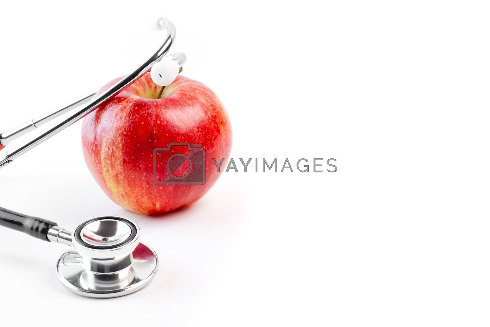 detail of medical stethoscope on red apple on a white background with space for text