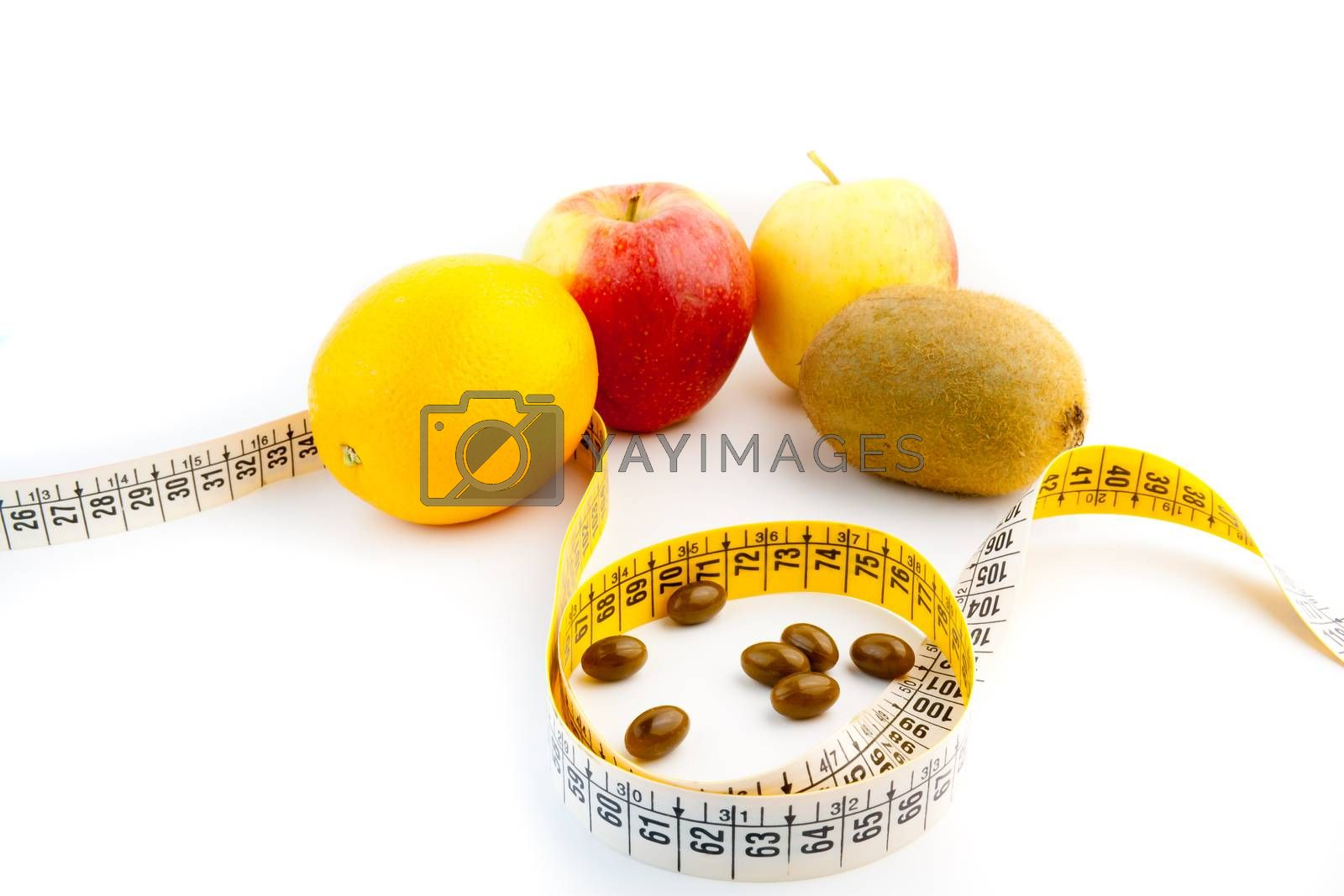 detail of pills and fruit  with measuring tape
