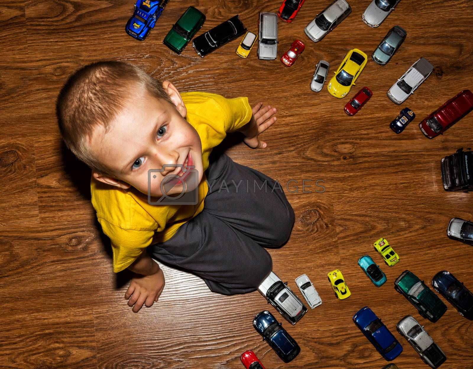 The photograph depicts a young boy with toy cars