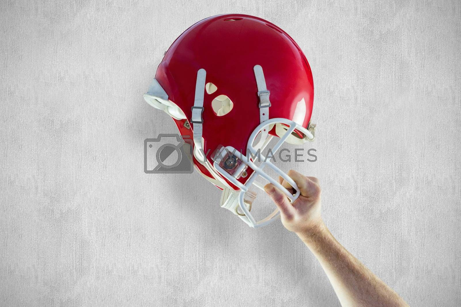 American football player holding up his helmet against white and grey background