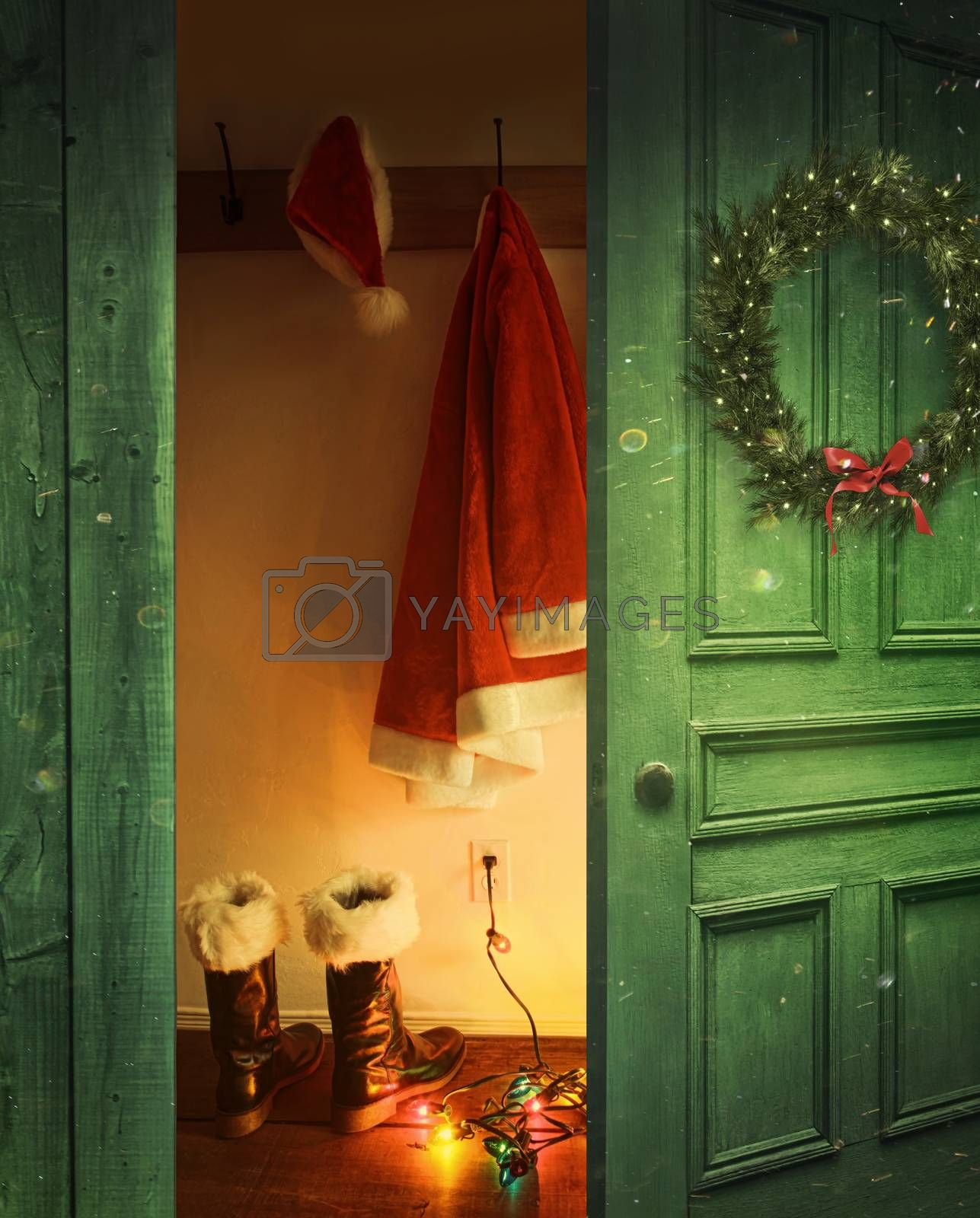 Open rustic door with Santa hat and outfit hanging on hooks