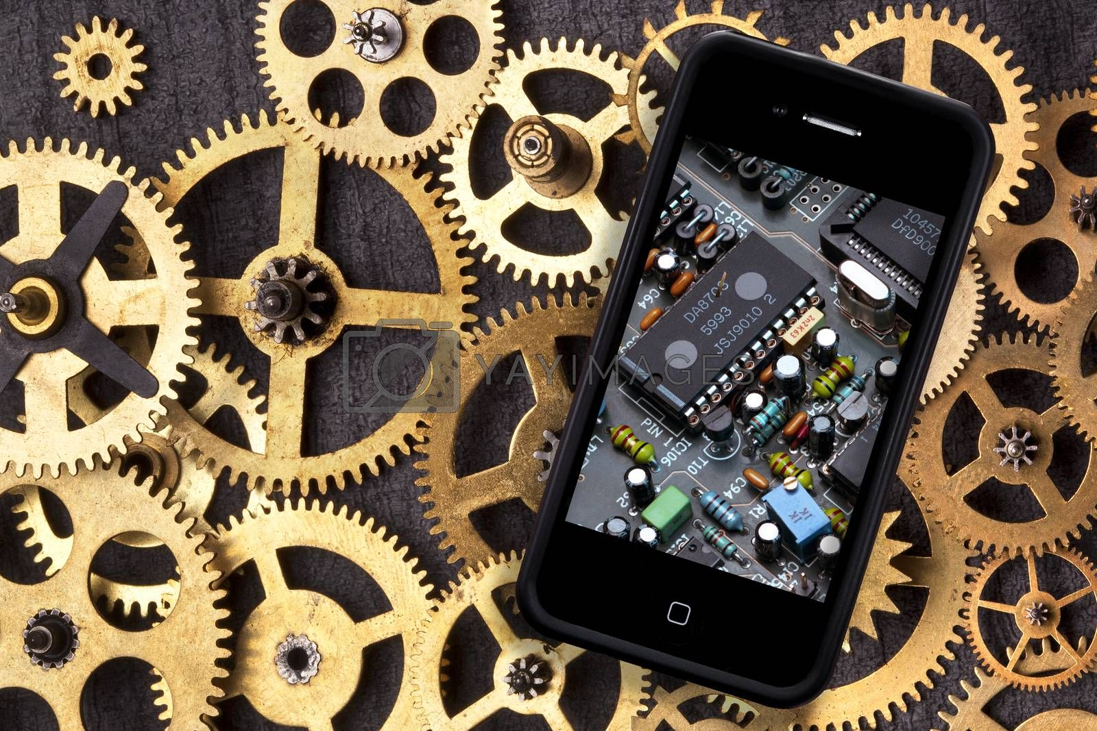 Old and New Technology - Old clockwork cogs and gears and a smartphone with digital technology