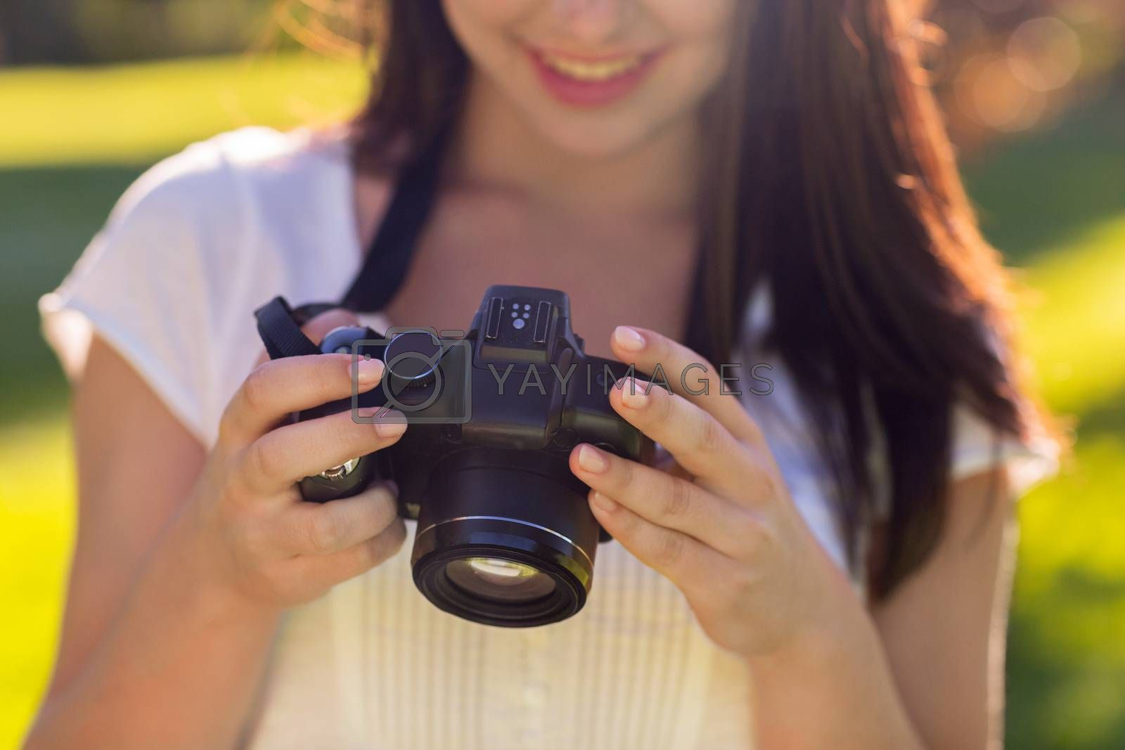 close up of young girl with photo camera outdoors by dolgachov