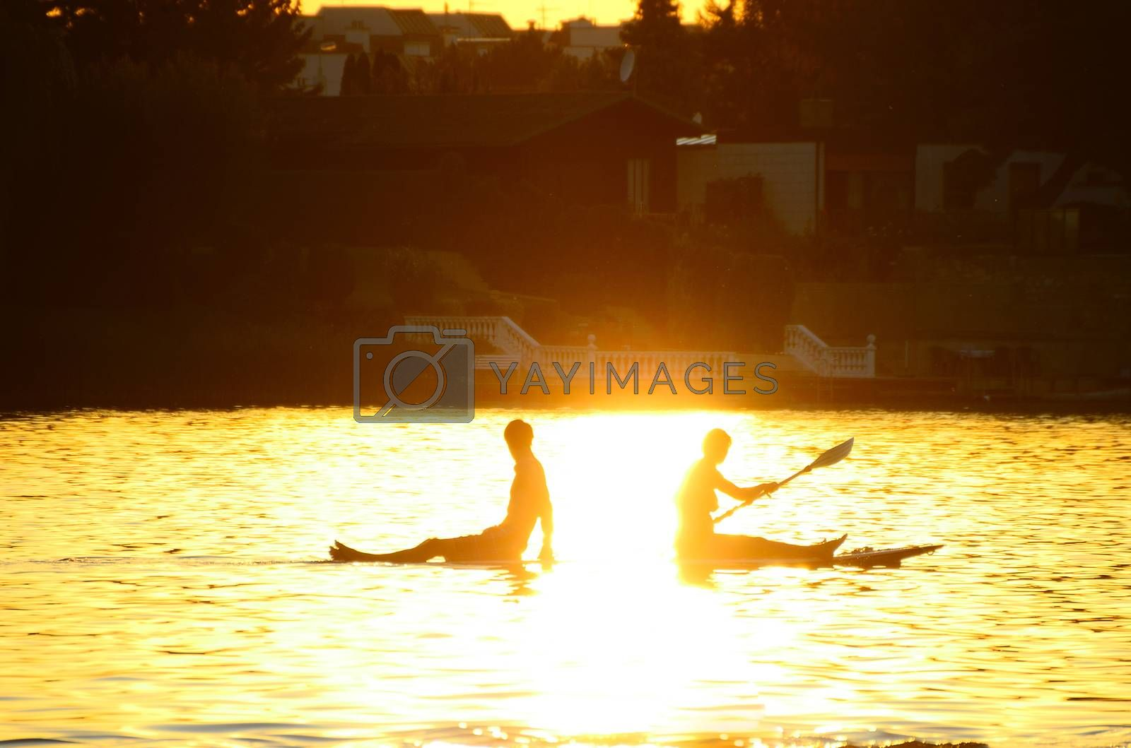Young couple sitting on surfboard and paddling in the sundown