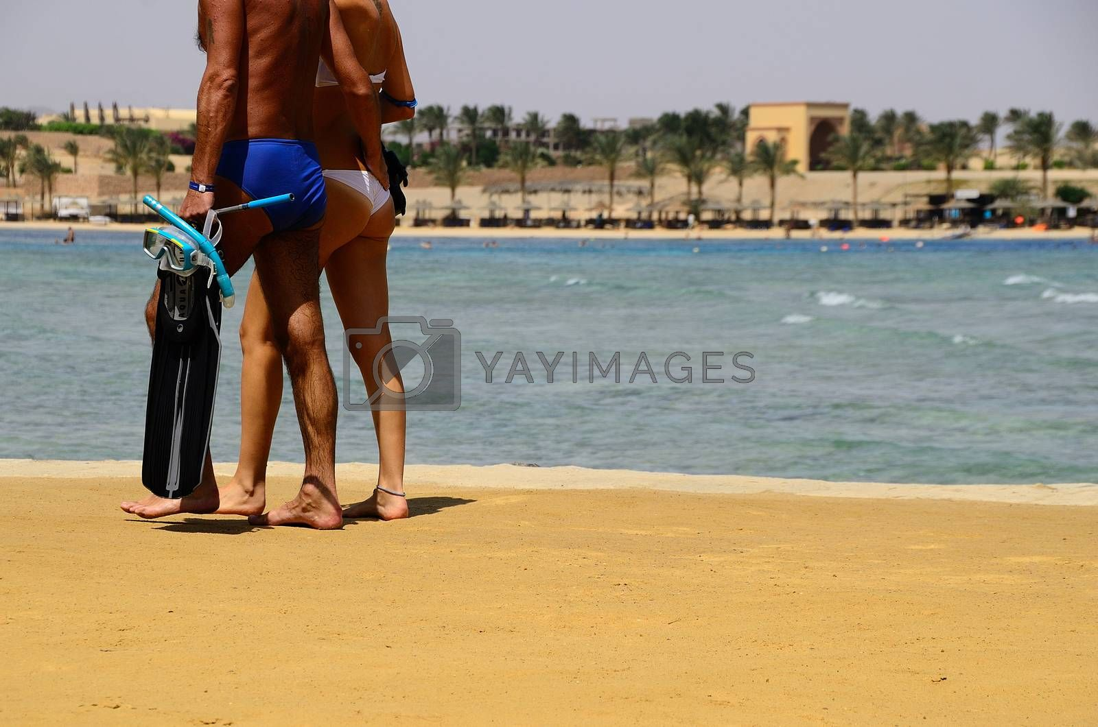 man and woman walk with snorkeling equipment on sandy beach on vacation