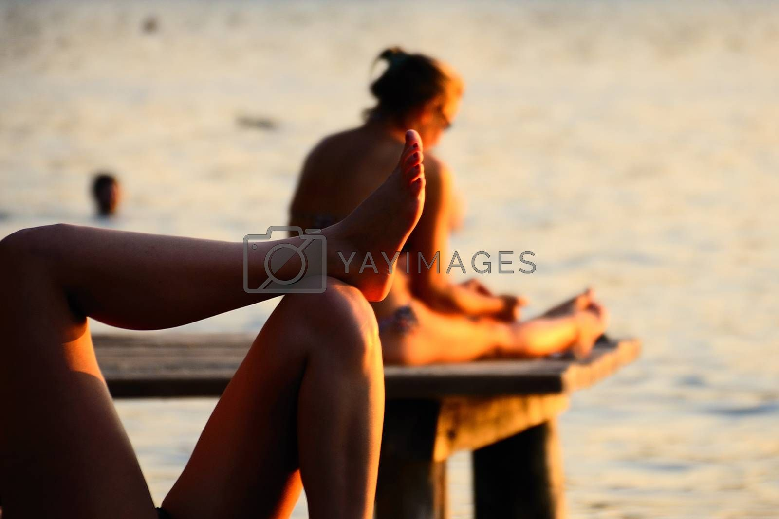 two women relaxing on the lake at sunset