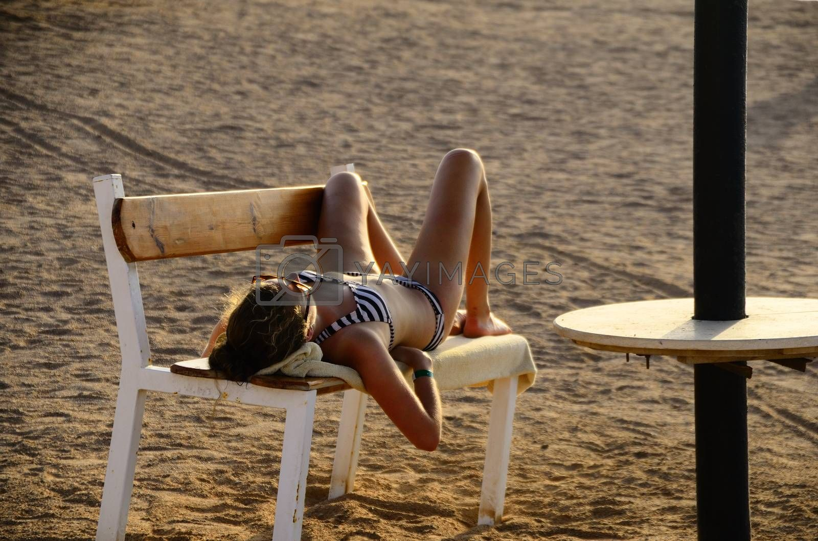 young woman in bikini sleeping on a bench on the sandy beach on vacation