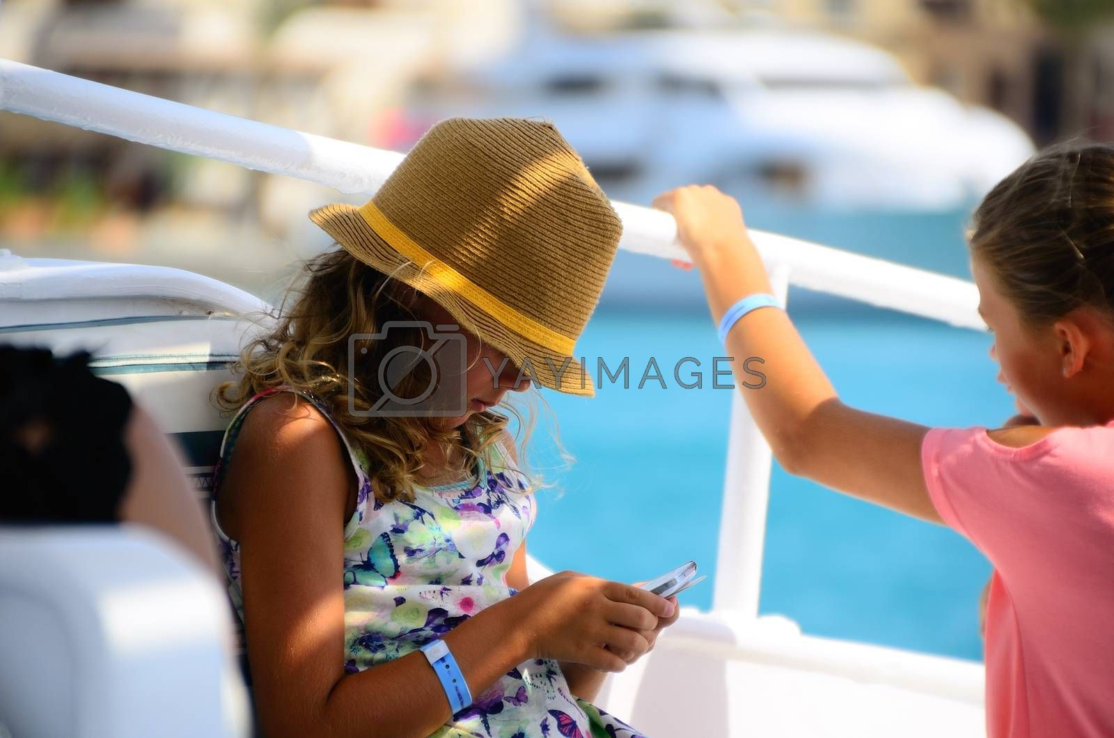 little girl with hat and mobile phone on vacation