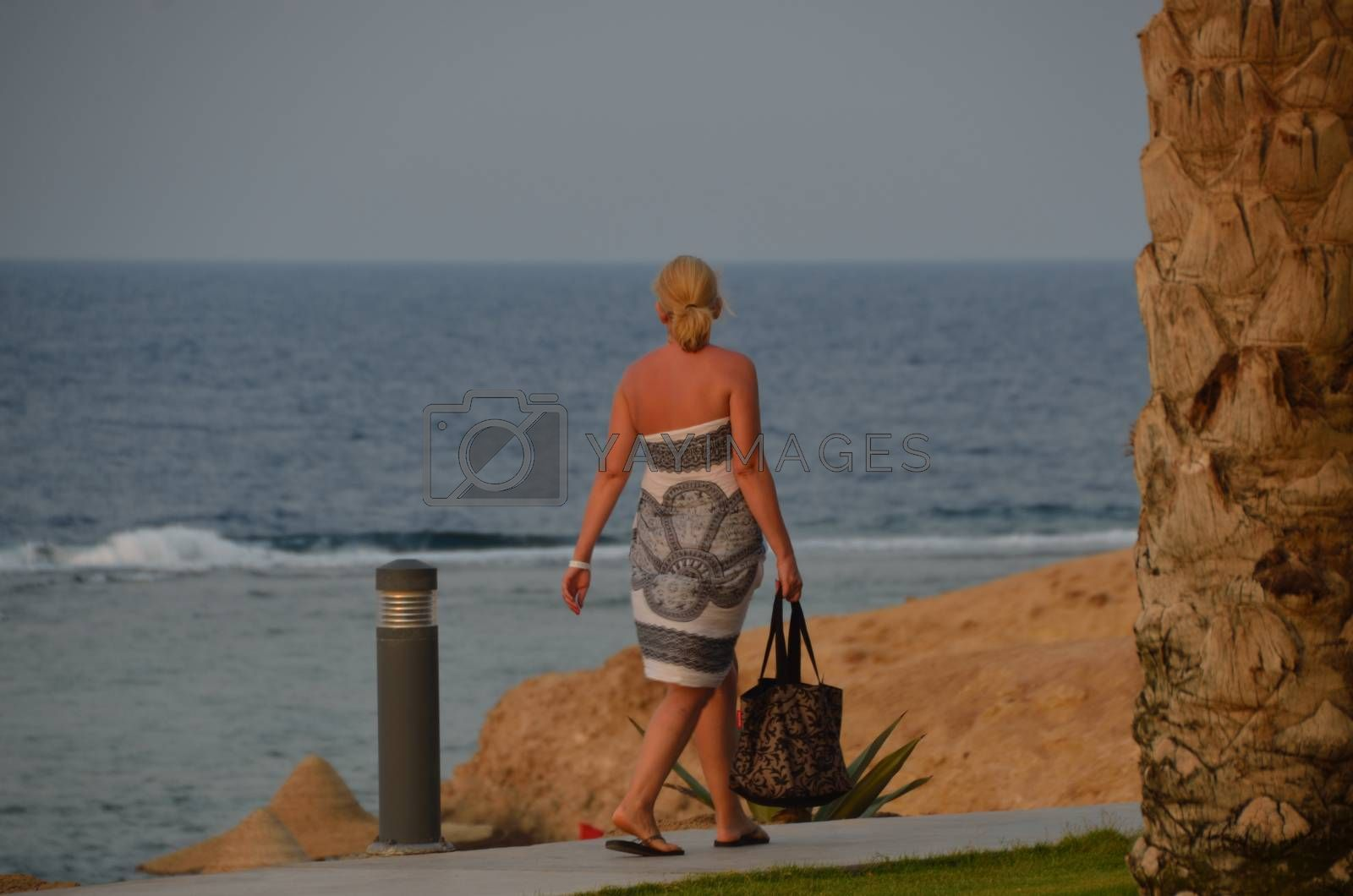 woman walking on the way to the beach on vacation