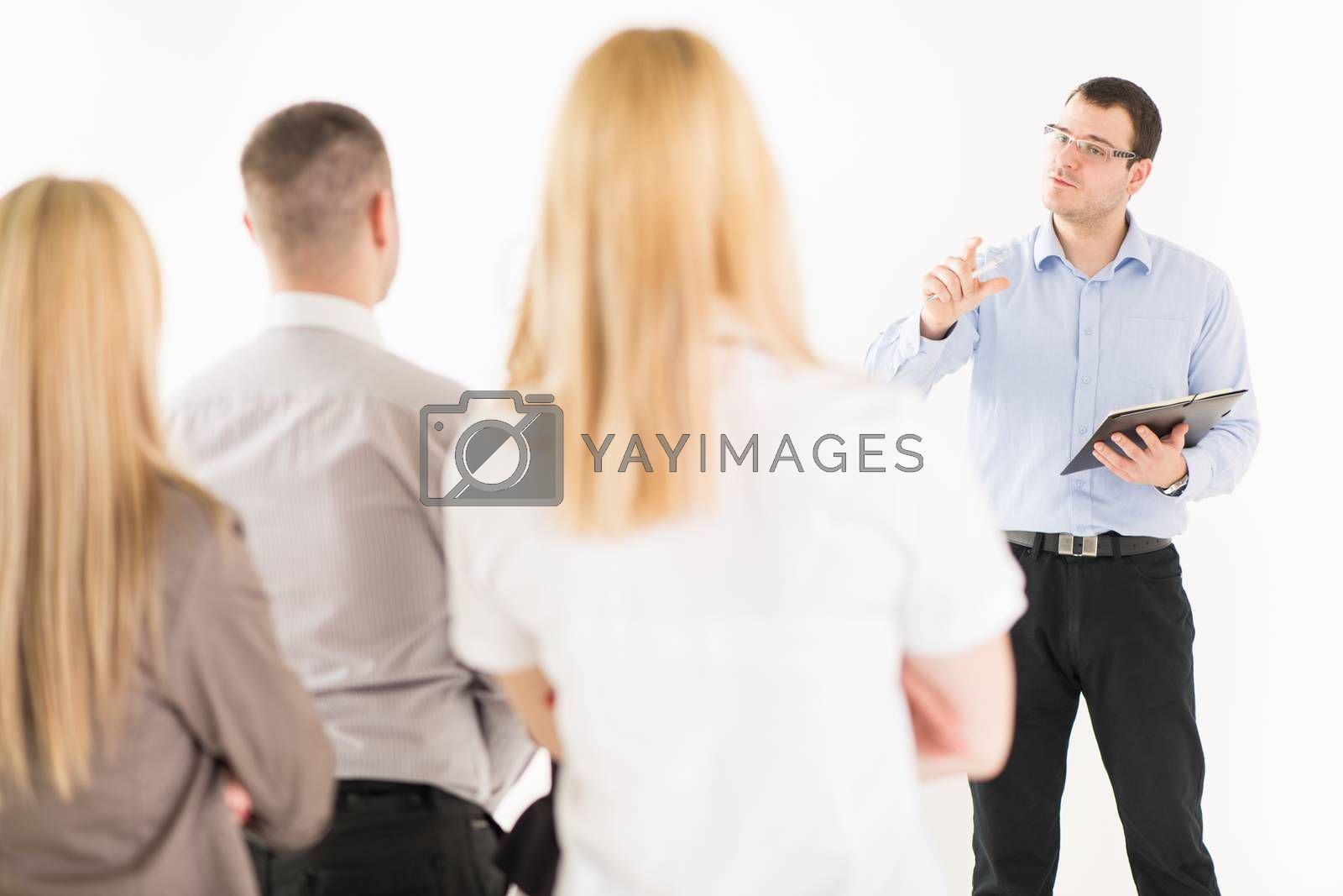 Friendly business man explaining plan of work in front of coworkers. The team is listening.