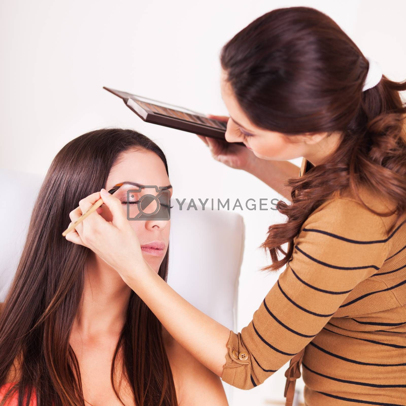 Female makeup artist darkening eyebrows with eyebrow pencil on Young Attractive woman.