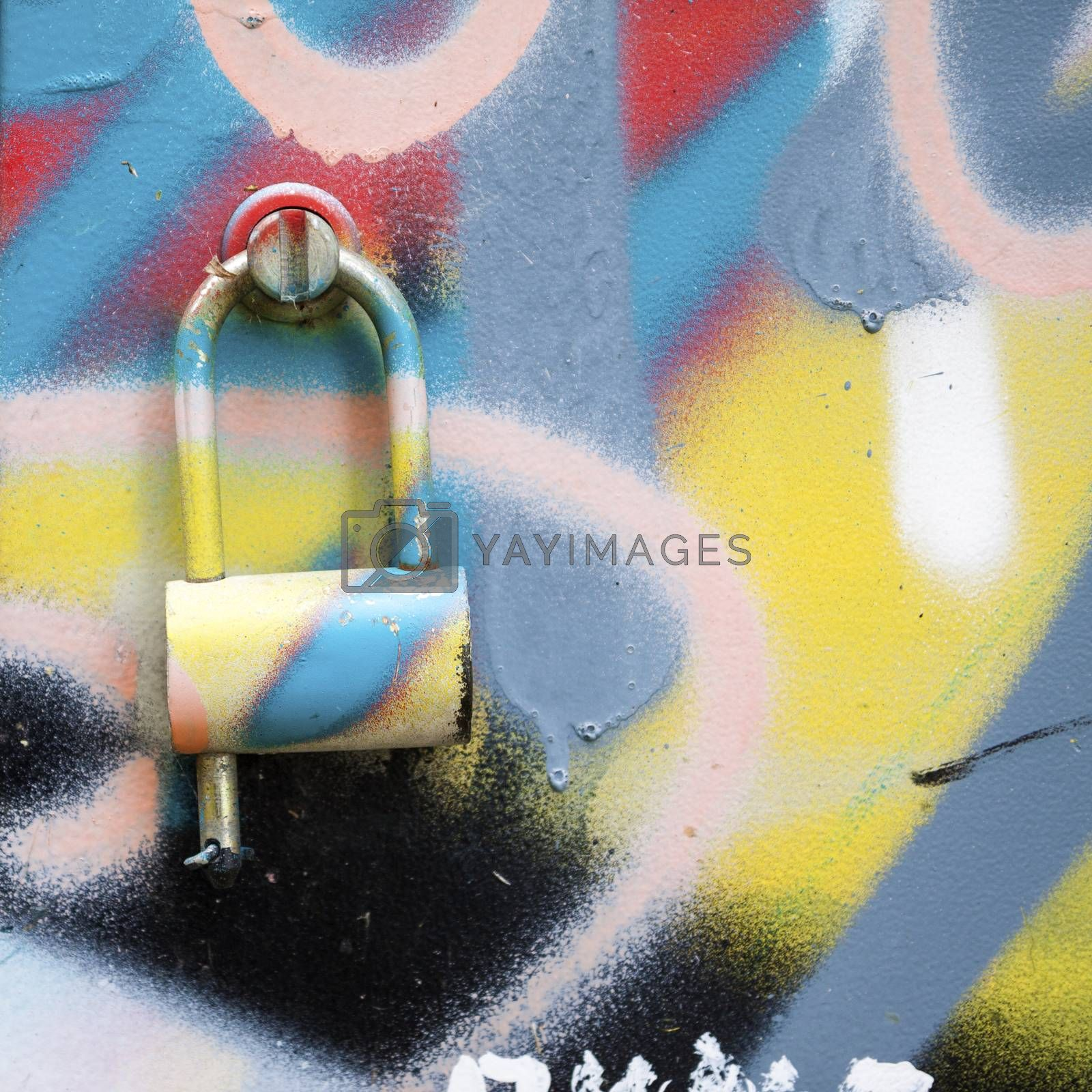 Colorful background of spray painted wall with metal lock