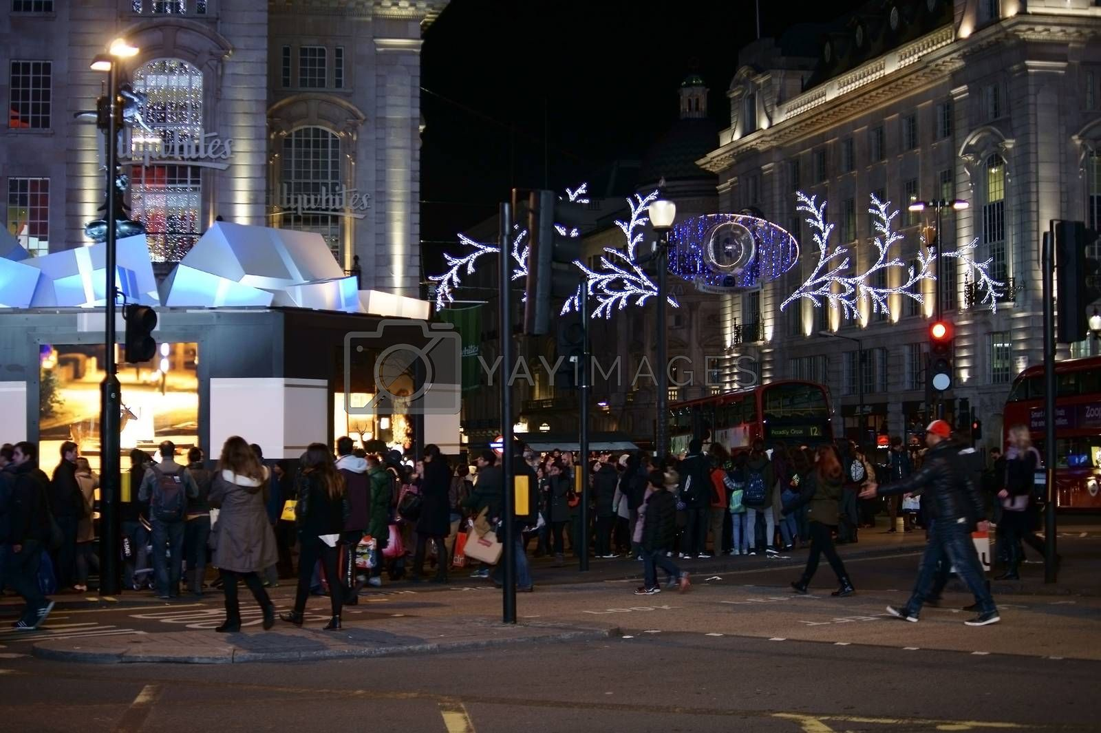 London, UK - November 29, 2014: A crowd of tourists and pedestrians are crossing a festively decorated intersection of the Piccadilly Circus on November 29, 2014 in London.