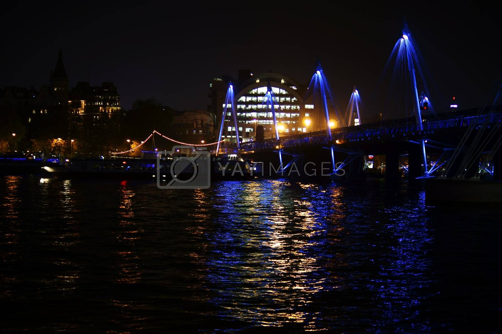 London, UK - November 29, 2014: The nocturnal illuminated Hungerford Bridge over the River Thames with the Charing Cross railway station on 29 November 2014 in London.