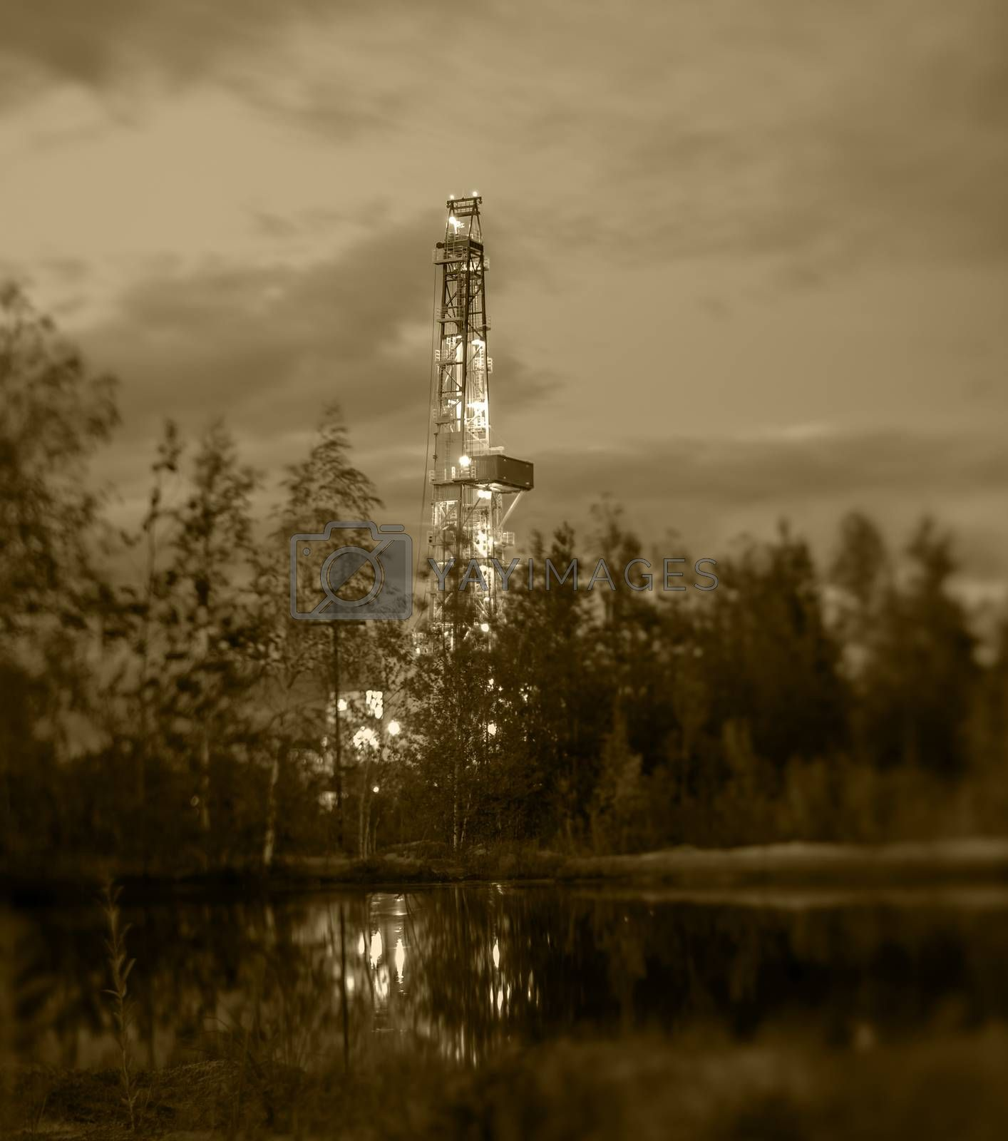 Night landscape with the drilling rig. Selective focus, shallow depth of field.