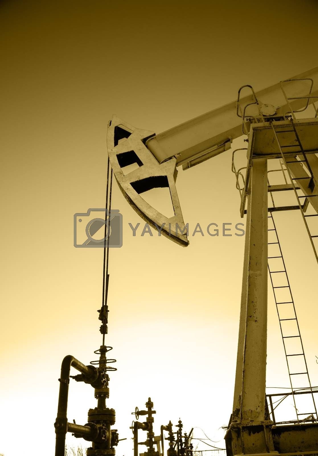 Pump jack and wellheads. Extraction of oil. Toned sepia.