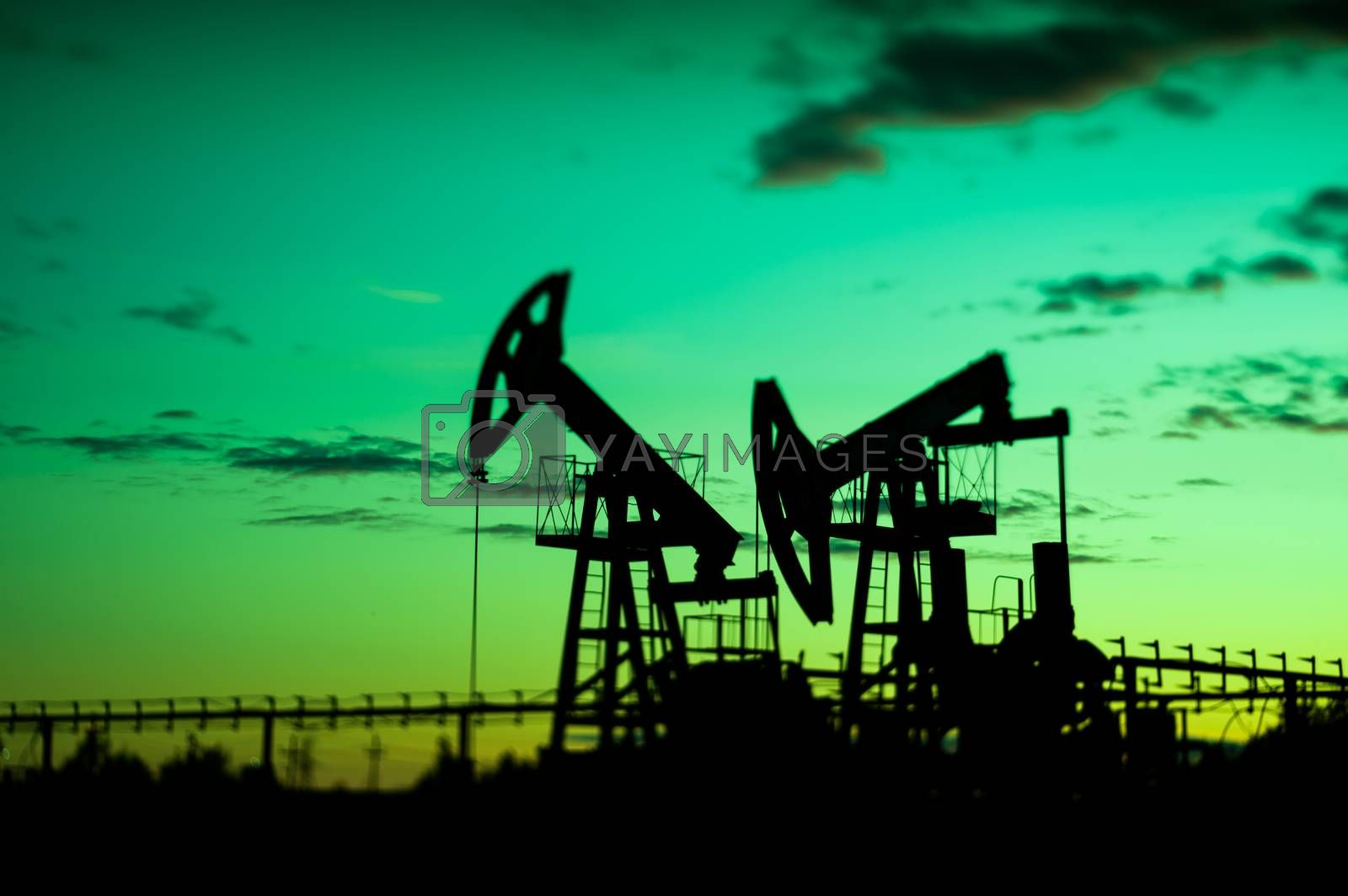 Oil pump jacks at sunset sky background. Selective focus, shallow depth of field.