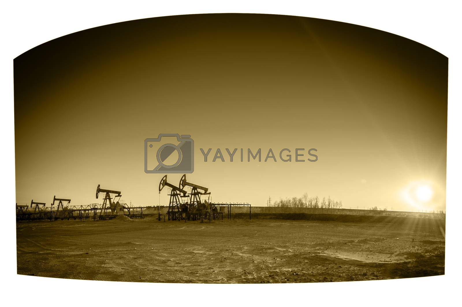 Oil pumps on the sunset sky background. Toned sepia.