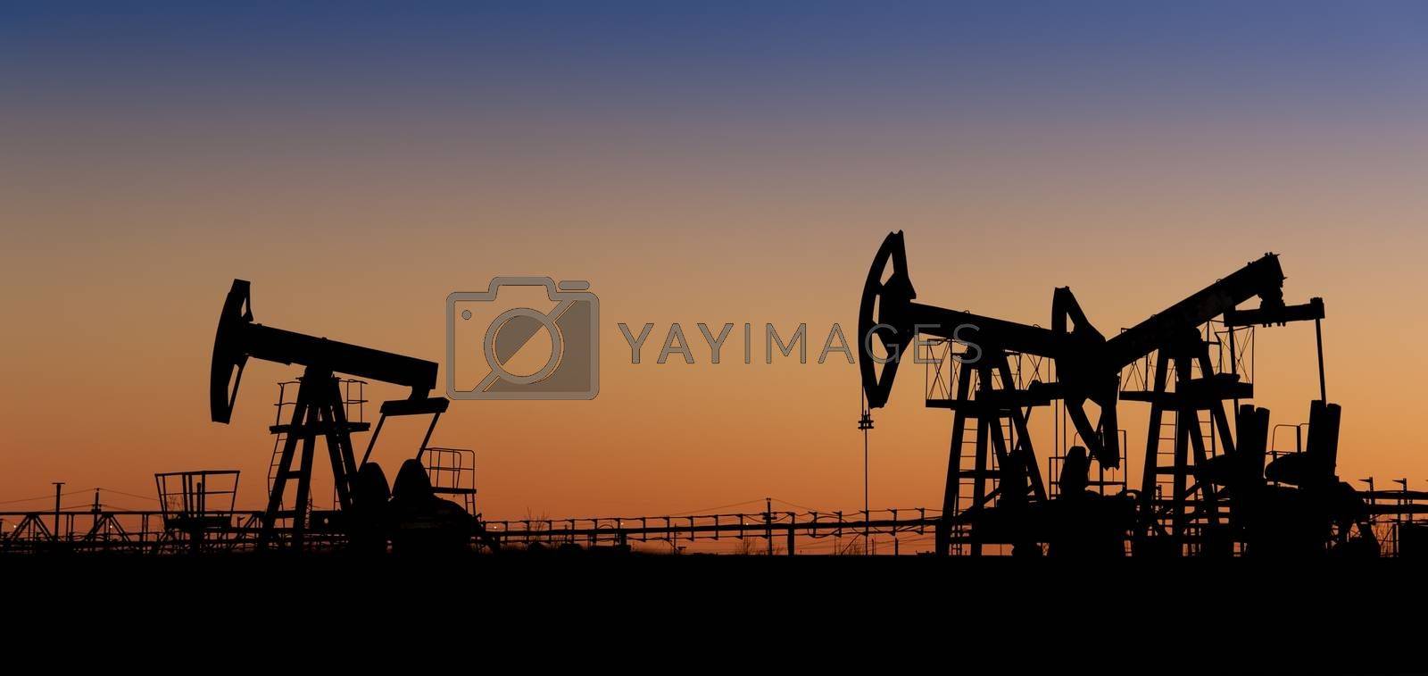 Pump jack group silhouette on a sunset sky background. Extraction of oil. Toned.