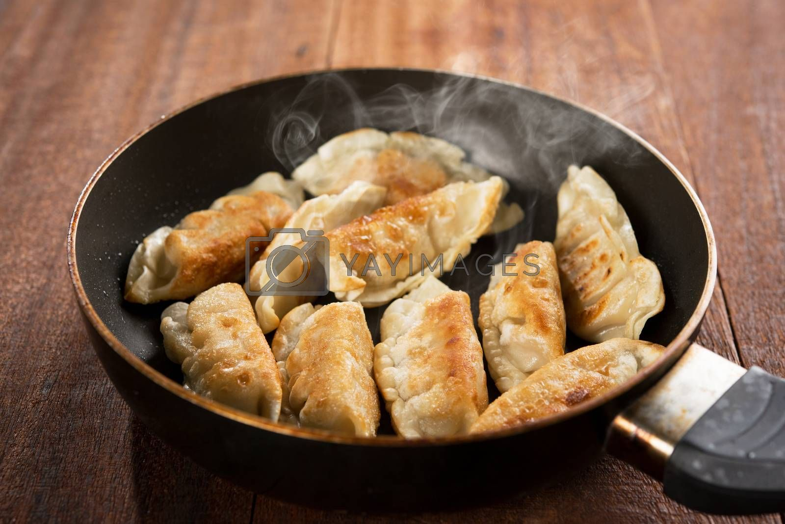 Close up cooking fried dumplings in a frying pan. Chinese food with hot steams, on rustic vintage wooden background.