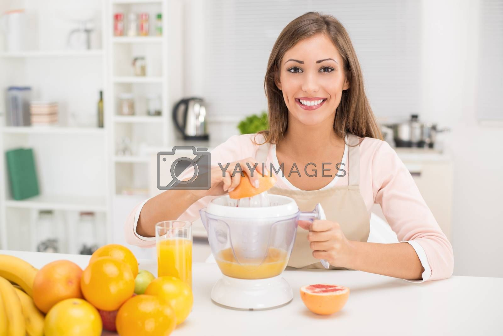 Beautiful young woman in the kitchen squeezing orange juice with an electric juicer. Looking at camera.