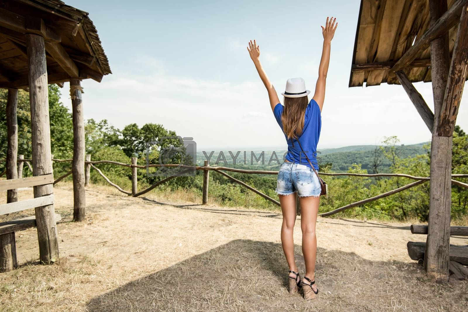 Cheerful woman on summer travel vacation standing by viewpoint with arms raised. Rear view.