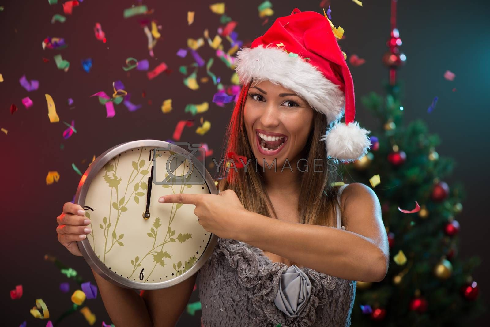 Cheerful beautiful woman celebrating New Year and showing midnight on the clock. She is having fun, confetti is in the air.