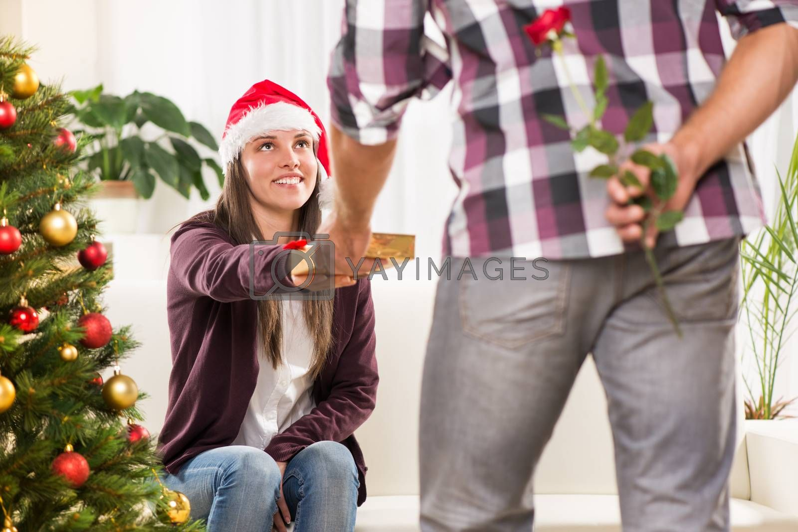 Young man gives his girlfriend a Christmas gift.