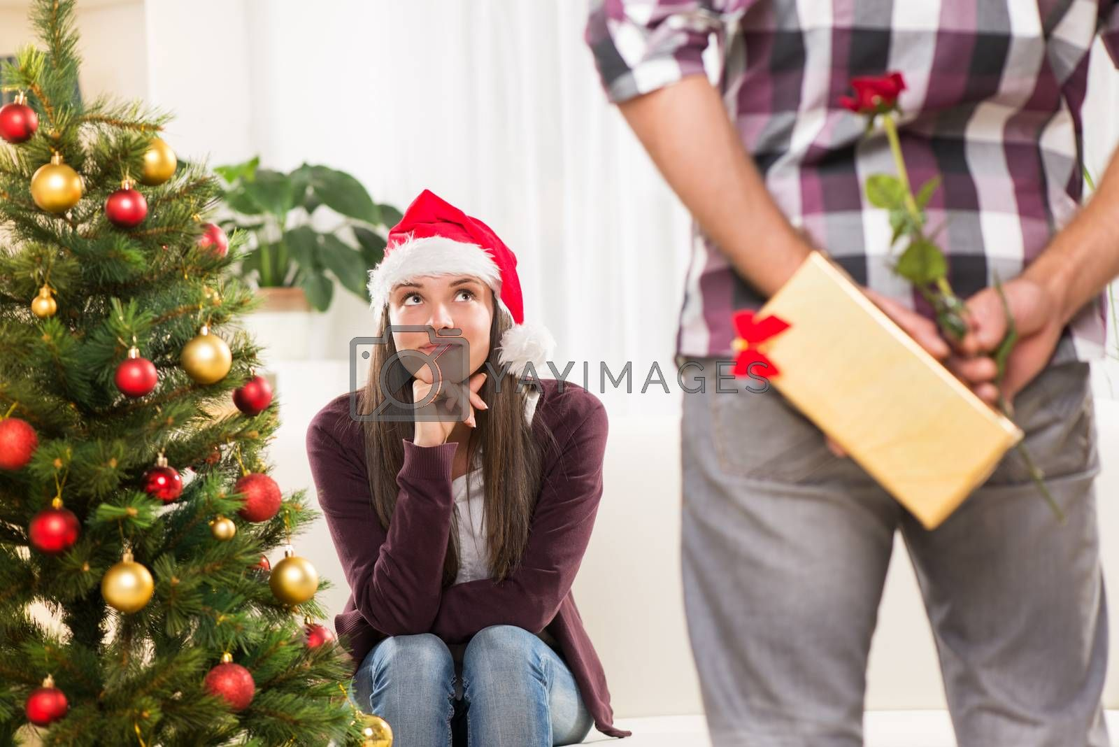 Young man has a Christmas present for his beautiful girlfriend and he wants to surprise her.