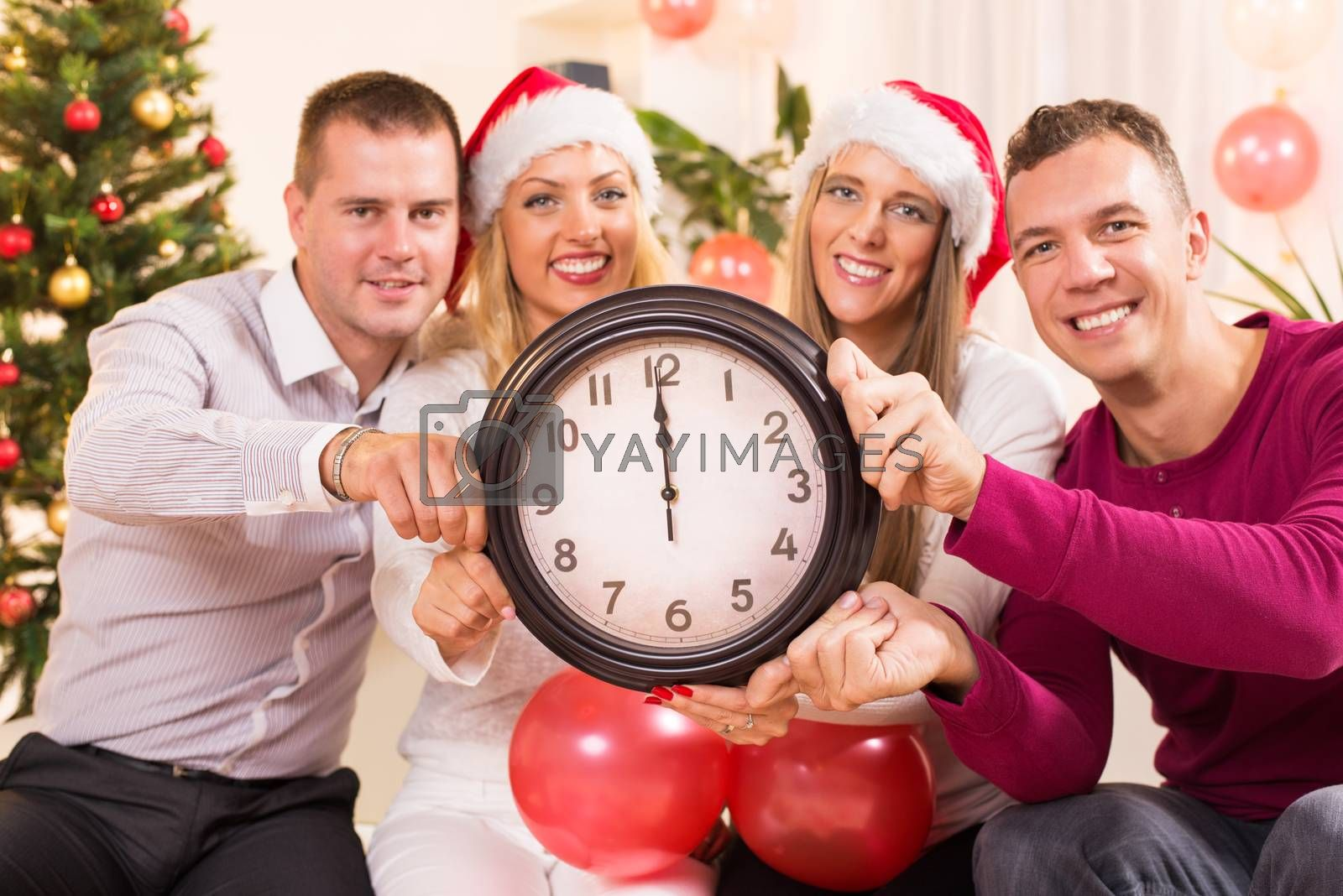 Happy friends Celebrating New Year in home interior and showing midnight on the clock. Selective Focus, focus on the clock.