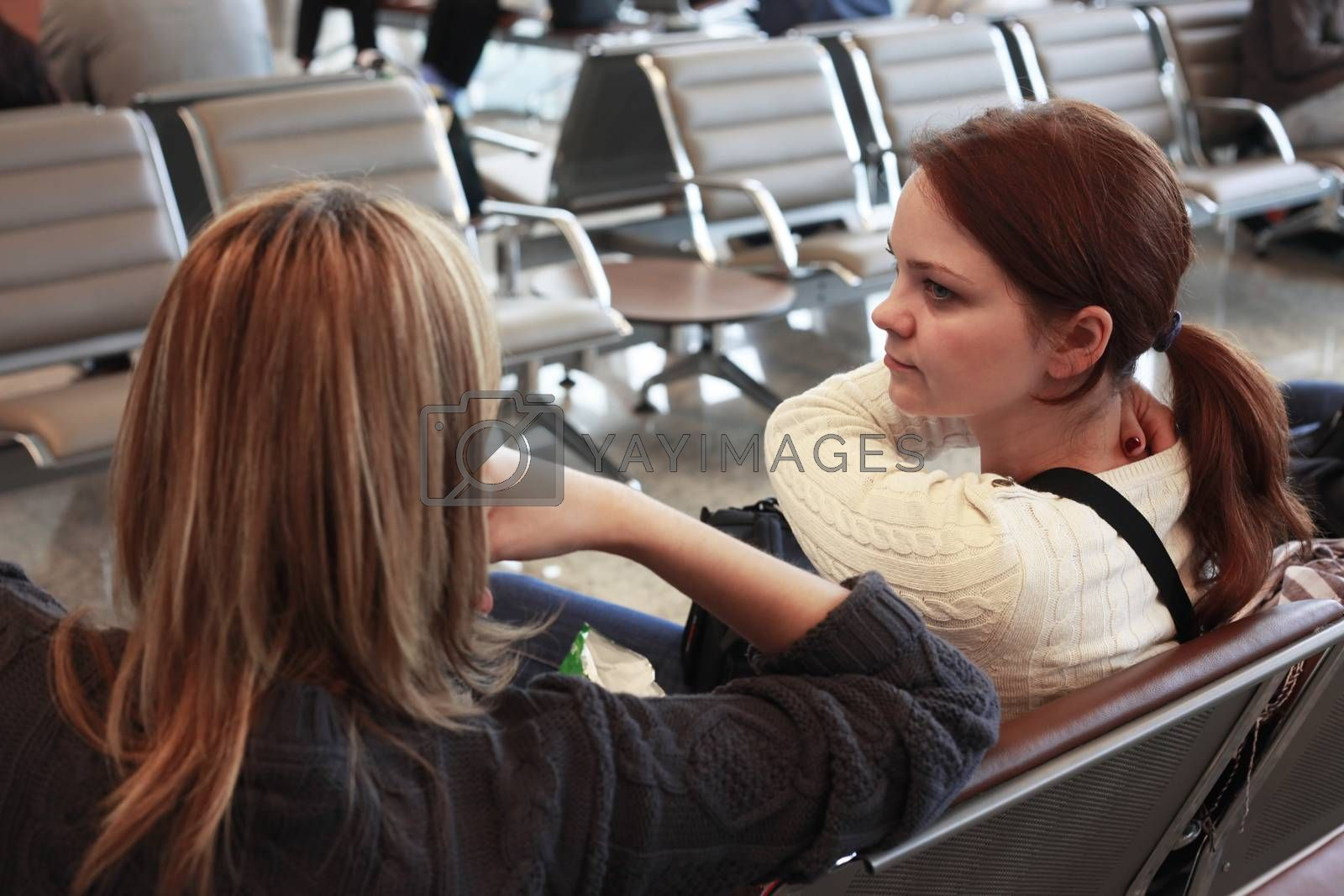 Two young girls in the waiting room at the airport