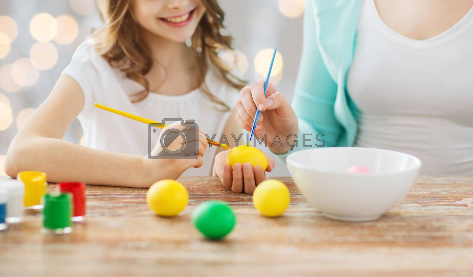 easter, family, holiday, people and childhood concept - close up of happy girl and mother with brushes coloring easter eggs over lights background