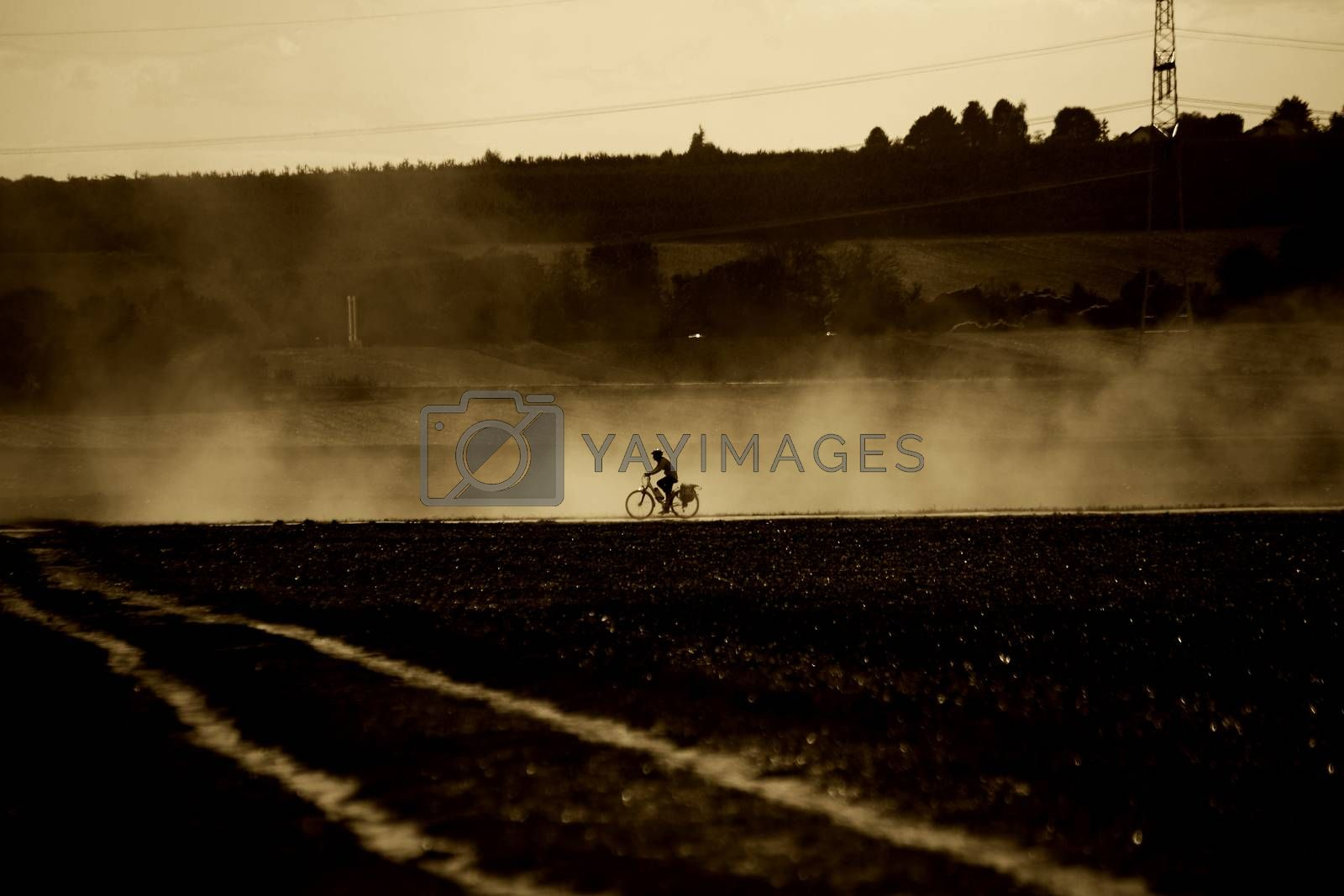 A cyclist rides through the sputtered vapor of a tractor.