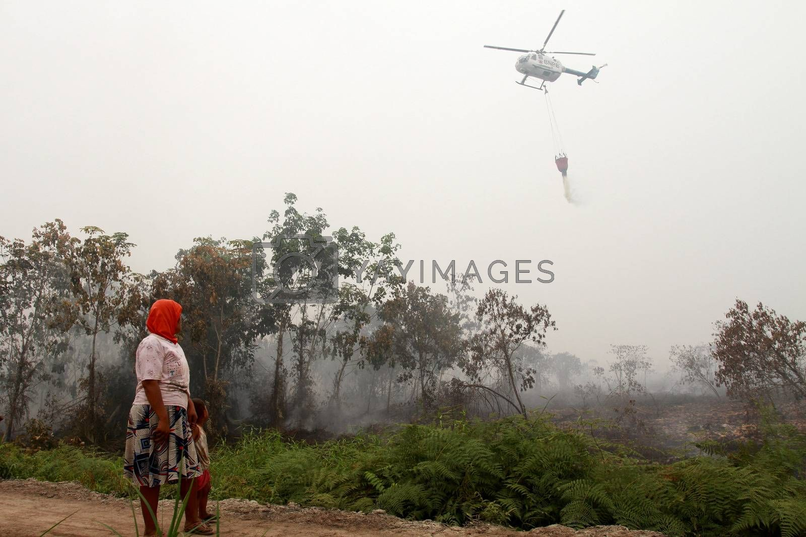 INDONESIA, Kubu Raya: An helicopter is helping to extinguish a fire at Kubu Raya district, in West Kalimantan province, on October 21, 2015. Indonesia launched its biggest operation ever to combat fires blanketing Southeast Asia in haze, an official said, with dozens of planes and thousands of troops battling the widespread blazes.