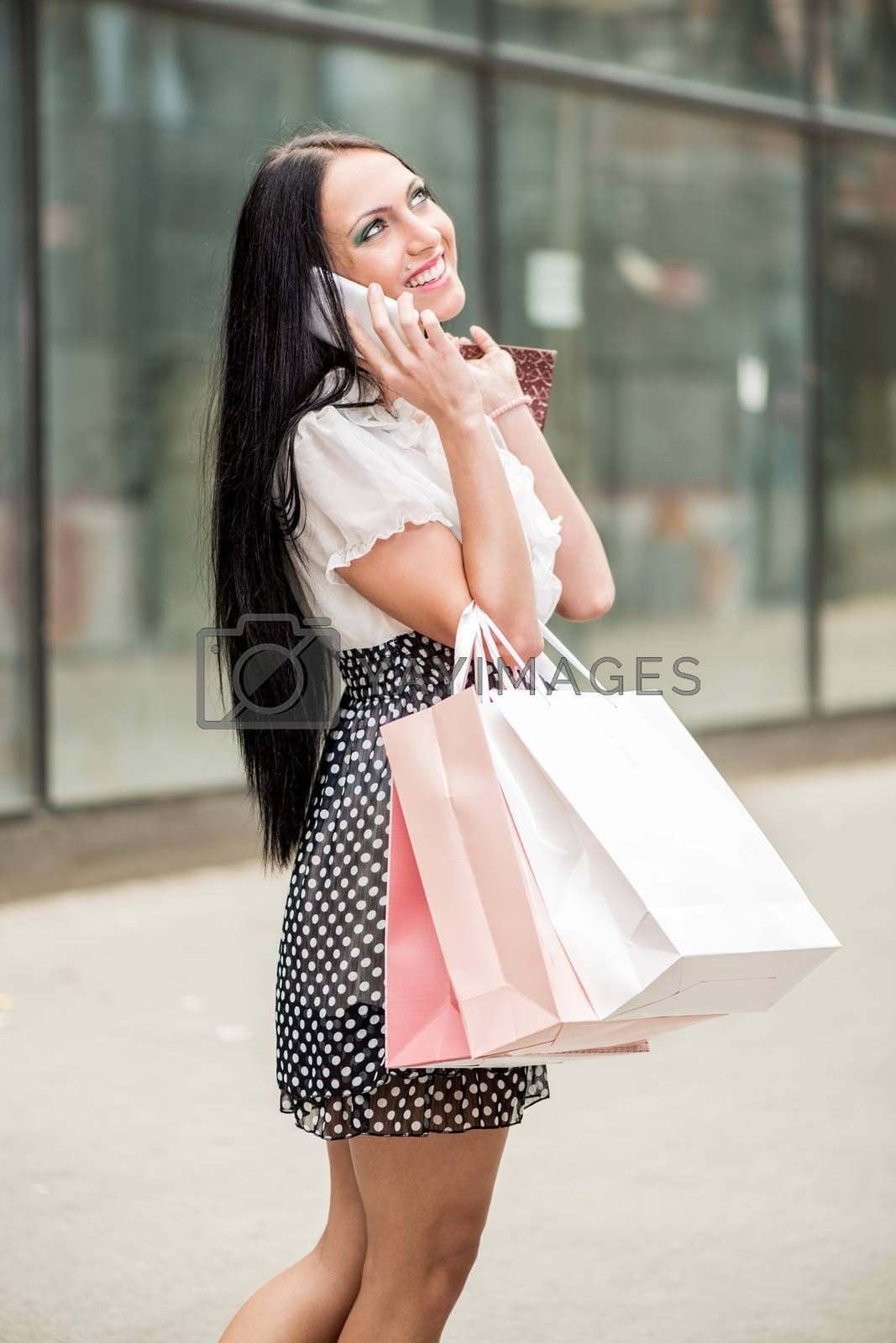 Happy girl in shopping walking out of shopping mall with bags in their hands and talking at smart phone.