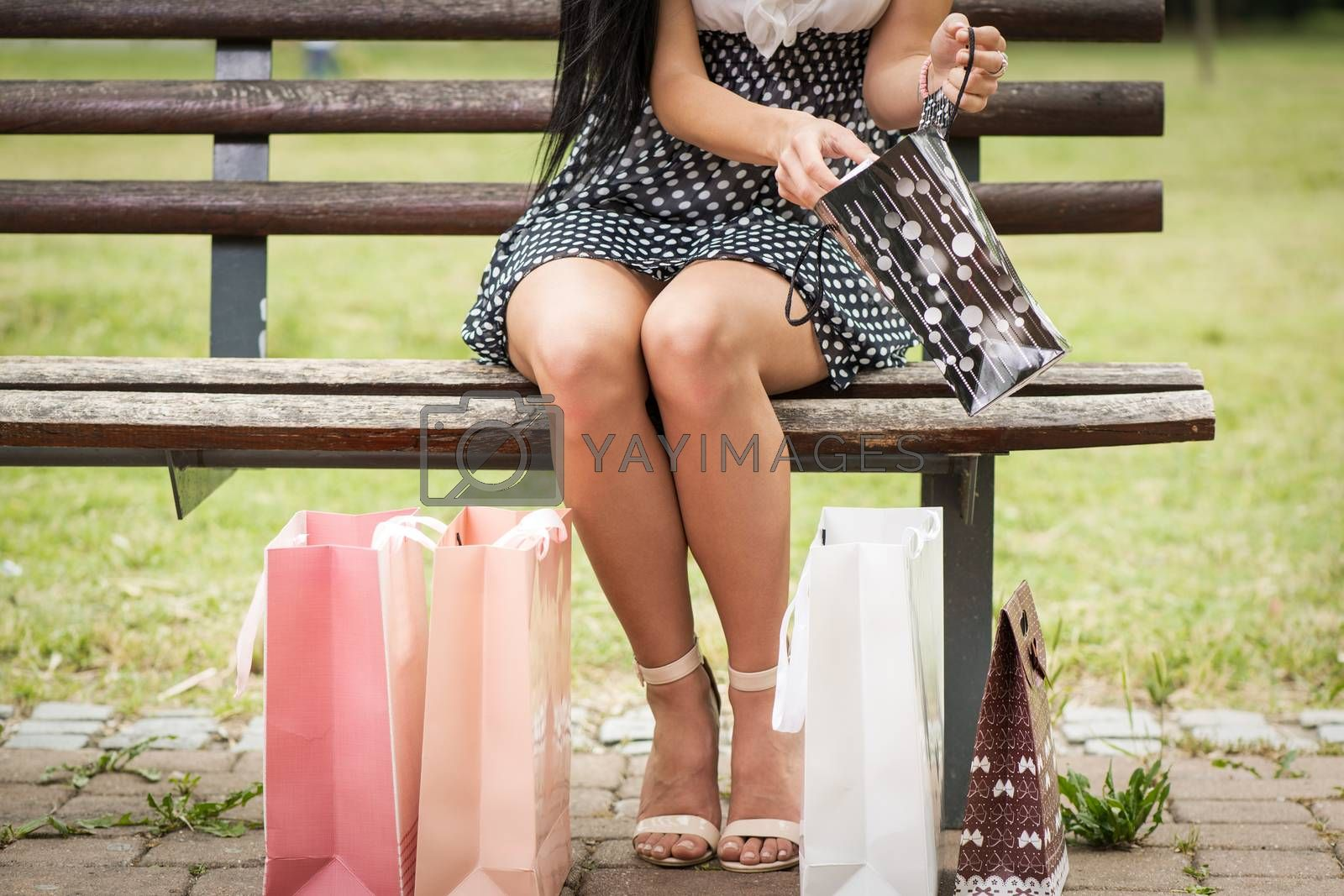 Close up of a girl legs after shopping with many shopping bags sitting on bench in the park.